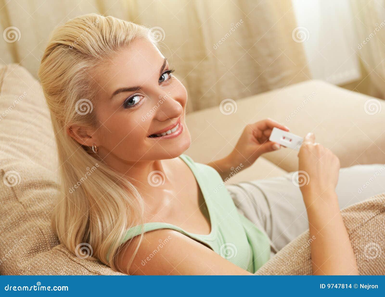 Mulher que prende o teste de gravidez positivo