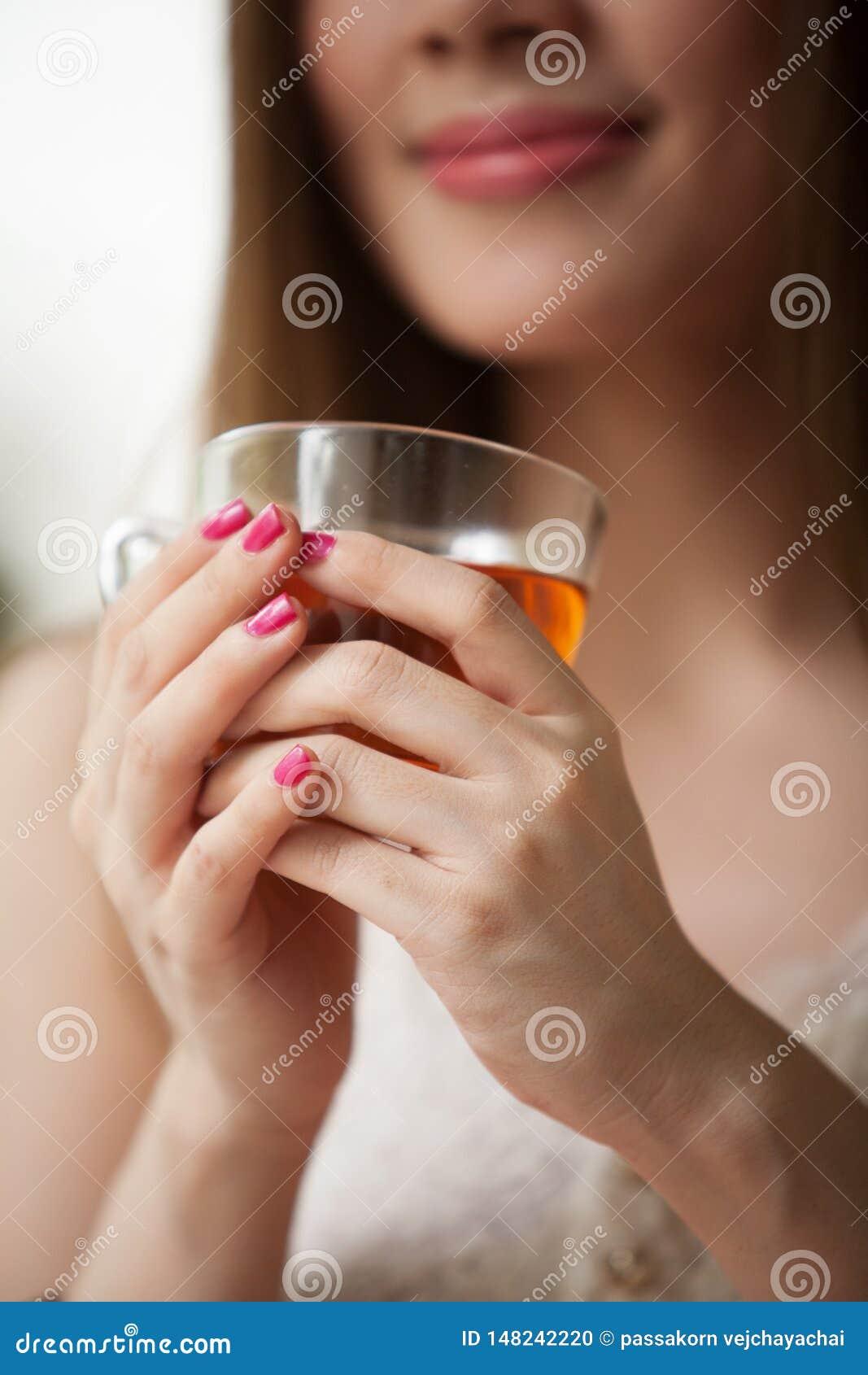Mulher que prende um copo do ch?