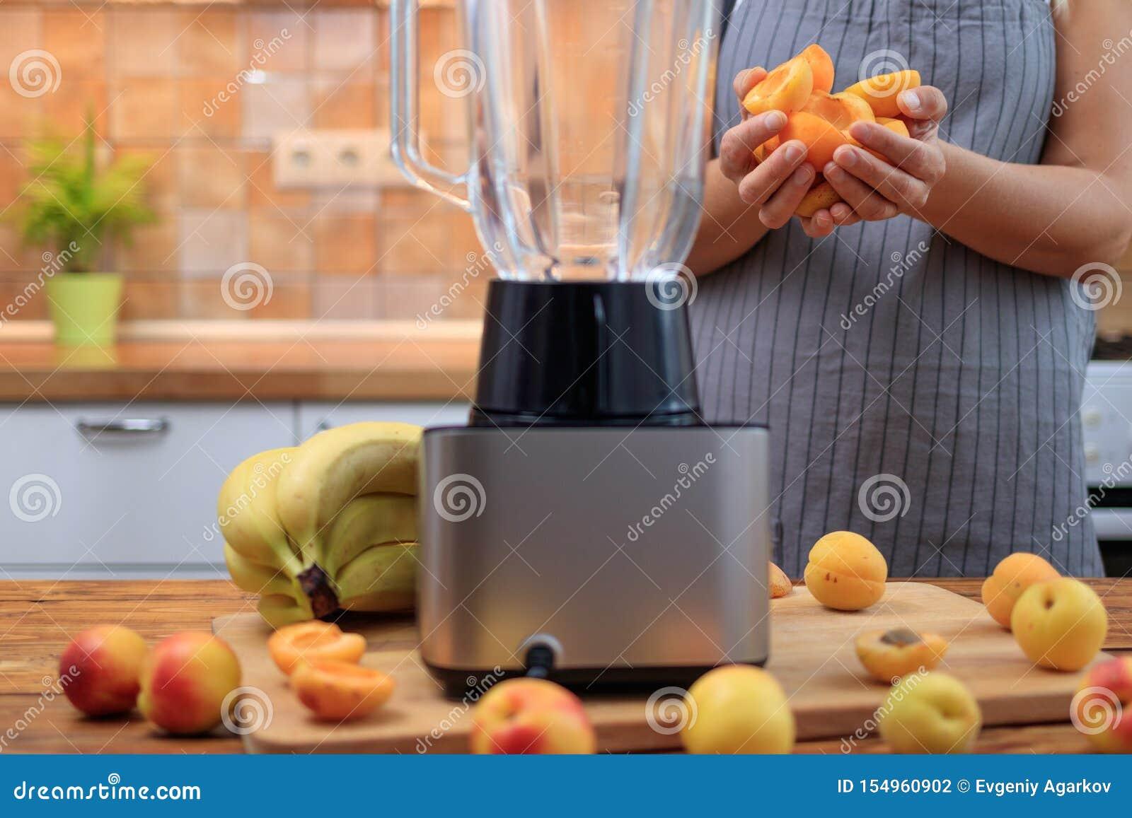 Mulher que prepara o batido ou o suco do abricó com frutos na cozinha