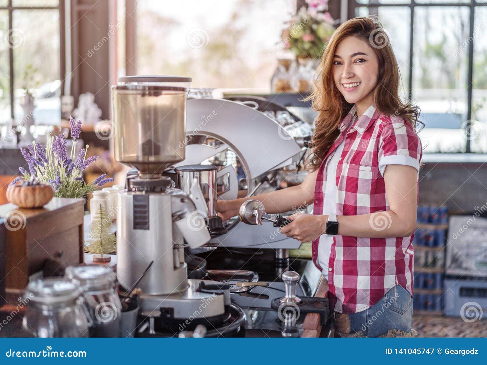 Mulher que prepara o café com a máquina no café