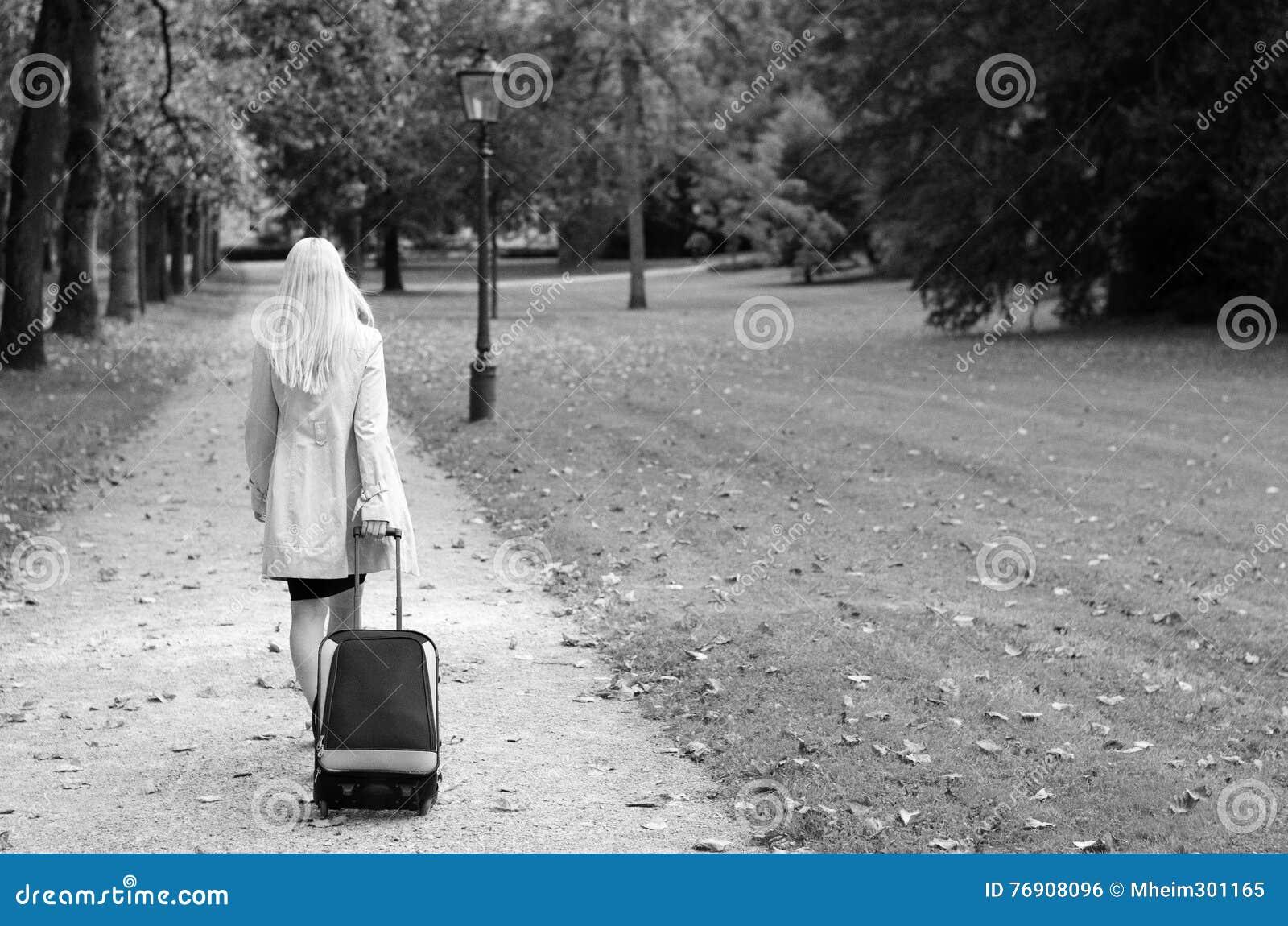 Mulher que puxa uma mala de viagem em preto e branco
