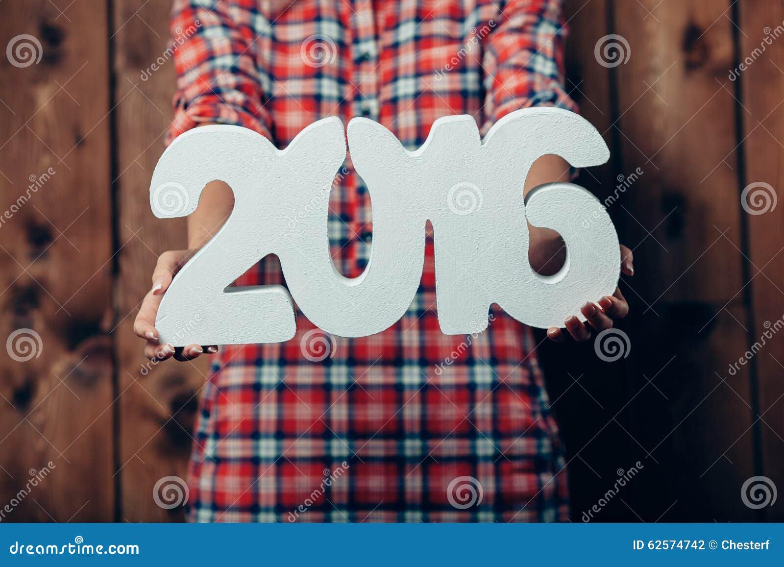 A mulher que realiza no ano novo 2016 das mãos numera