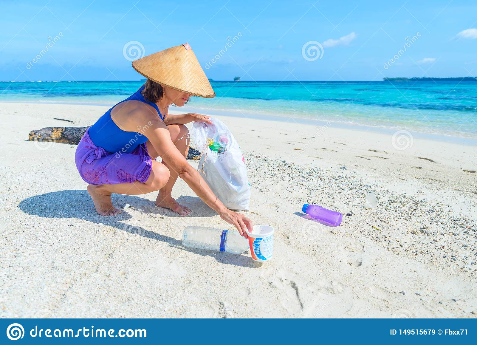 Mulher que recolhe garrafas pl?sticas na praia tropical bonita, mar de turquesa, dia ensolarado, reciclando o conceito dos desper