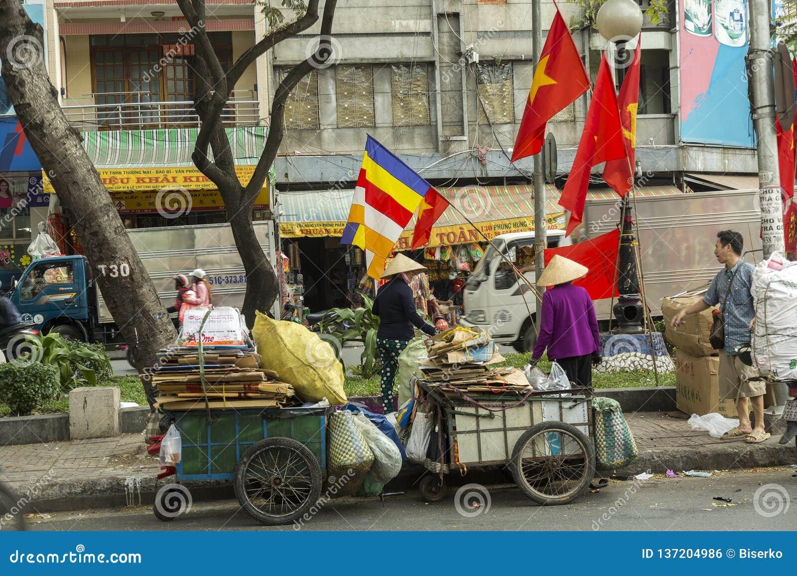 Mulher que recolhe o papel em Ho Chi Minh, Vietname