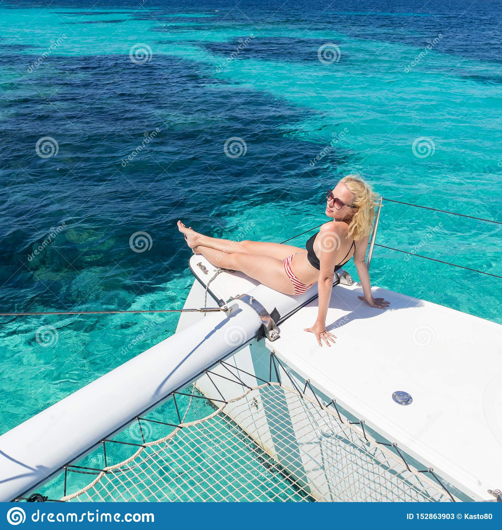 Mulher que relaxa em um cruzeiro da naviga??o do ver?o, assento em um catamar? luxuoso perto do Sandy Beach branco perfeito da im