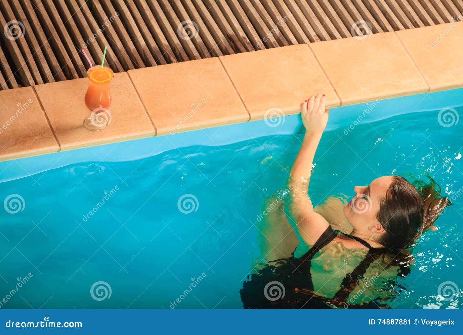Mulher que relaxa na borda da piscina lazer