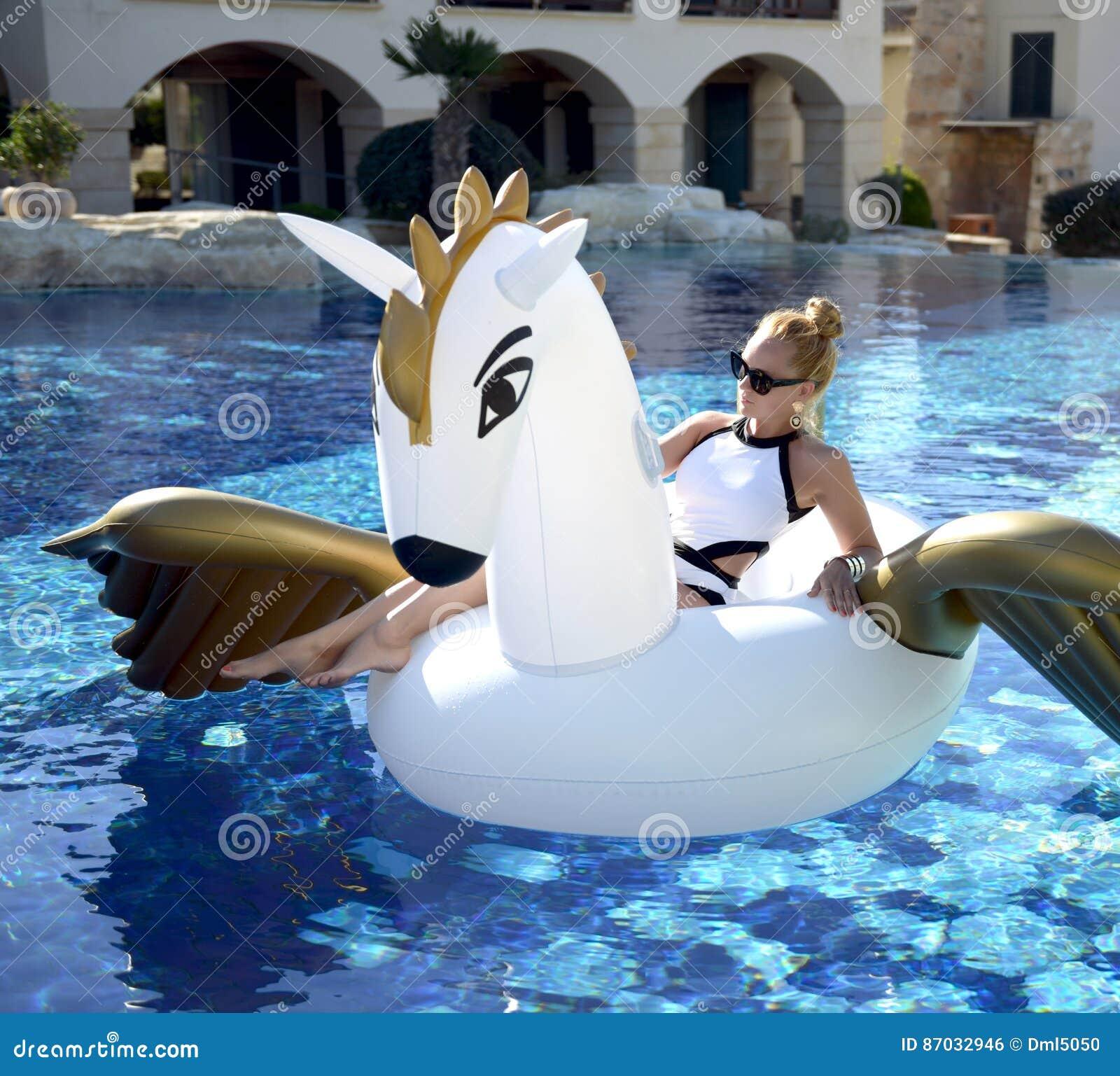 Mulher que relaxa na estância luxuosa da piscina com bi enorme