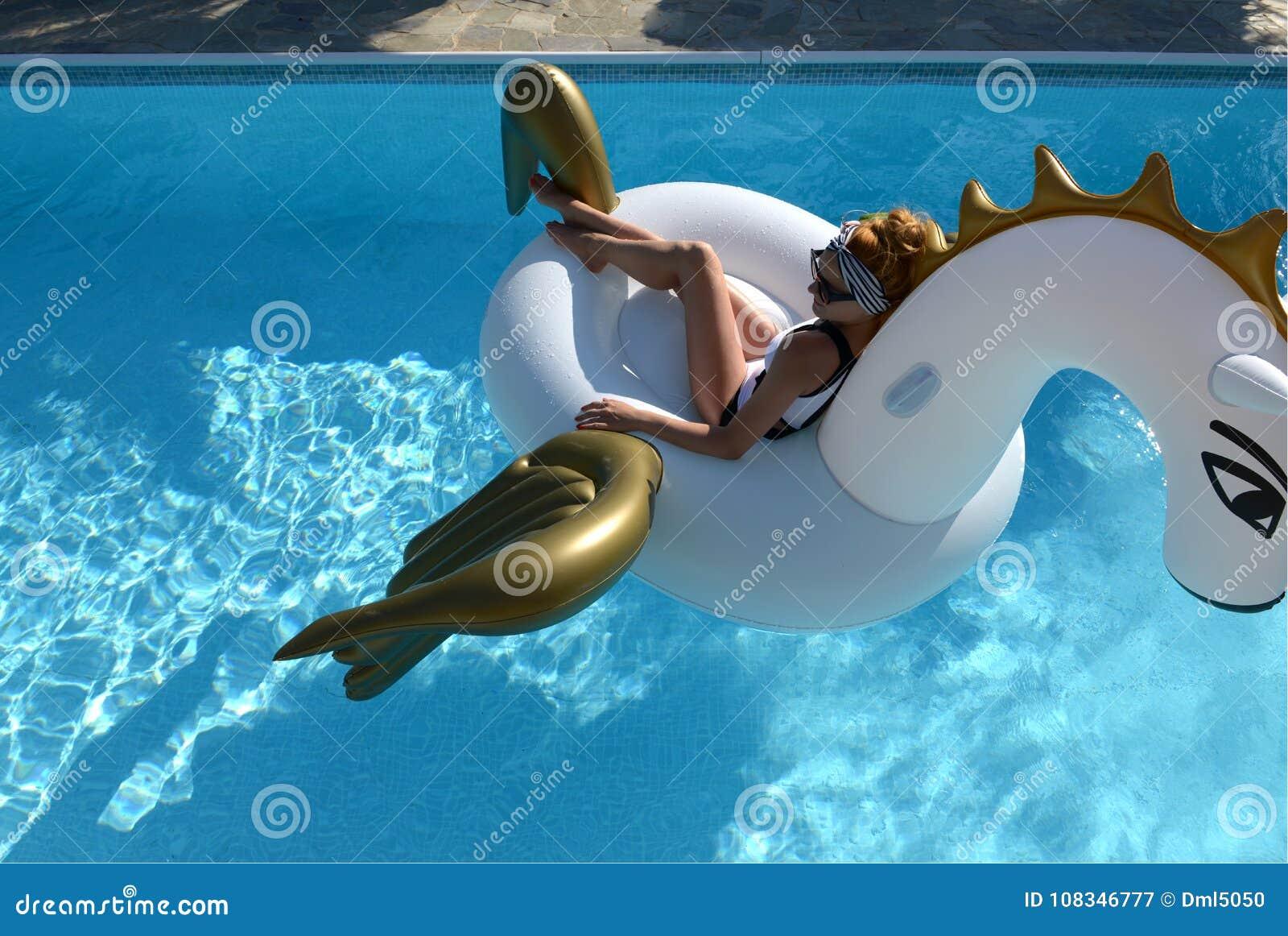 Mulher que relaxa na estância luxuosa da piscina no unicórnio inflável grande que flutua o flutuador de pegasus