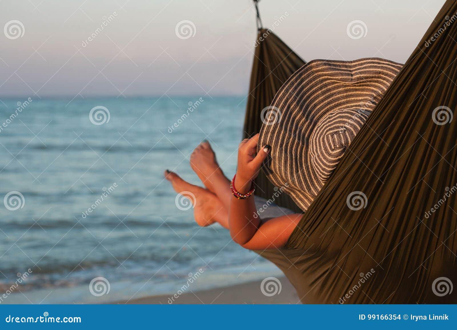 Mulher que relaxa na rede com o banho de sol do chapéu em férias Na perspectiva do mar no sol de ajuste