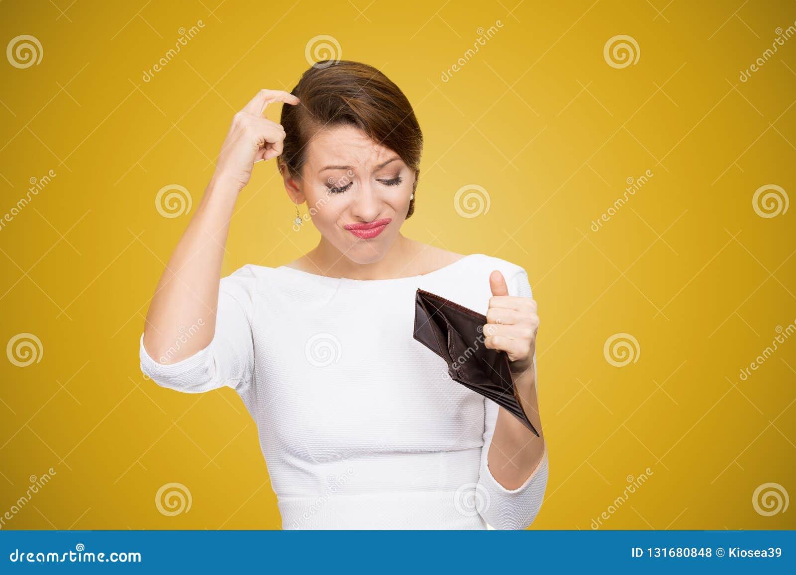 Mulher que risca na cabeça e que olha para dentro da carteira vazia que não tem nenhum dinheiro