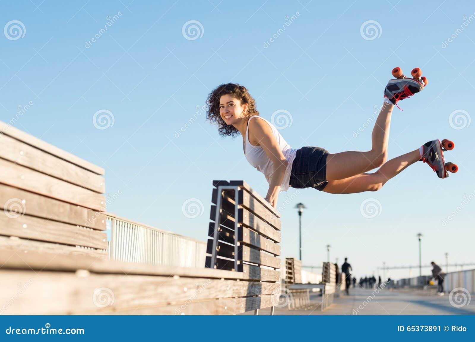 A mulher que salta com patins de rolo