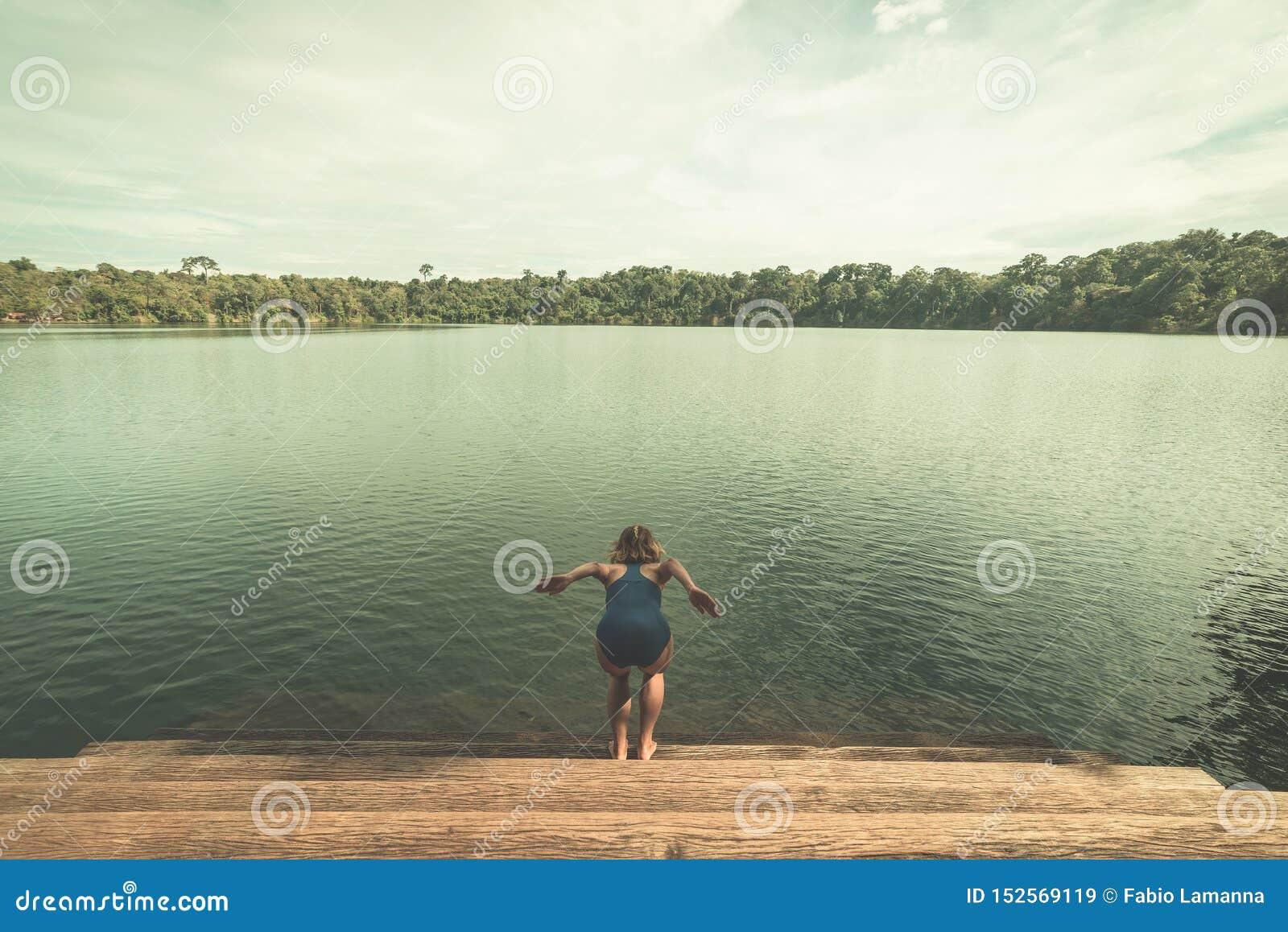 A mulher que salta na água do lago vulcânico cercada pela floresta em Banlung, Camboja, destino do curso Estilo tonificado do vin