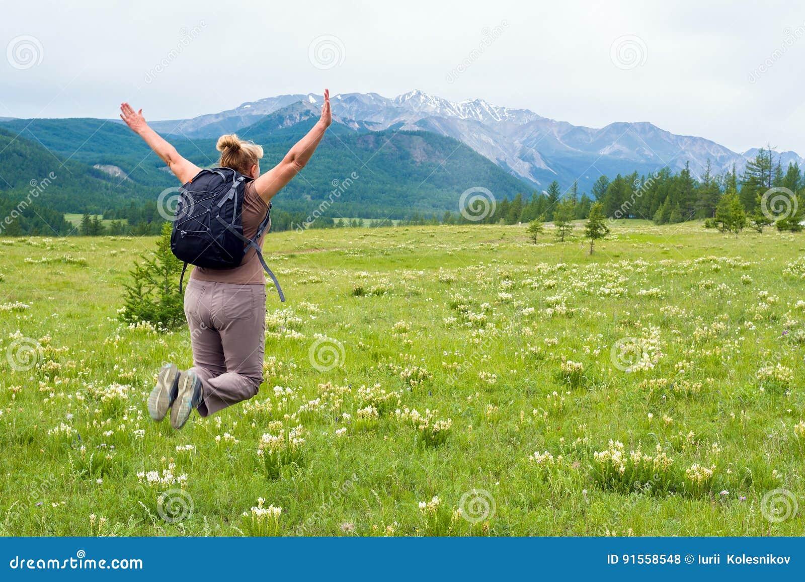 A mulher que salta para a alegria que olha a beleza da natureza