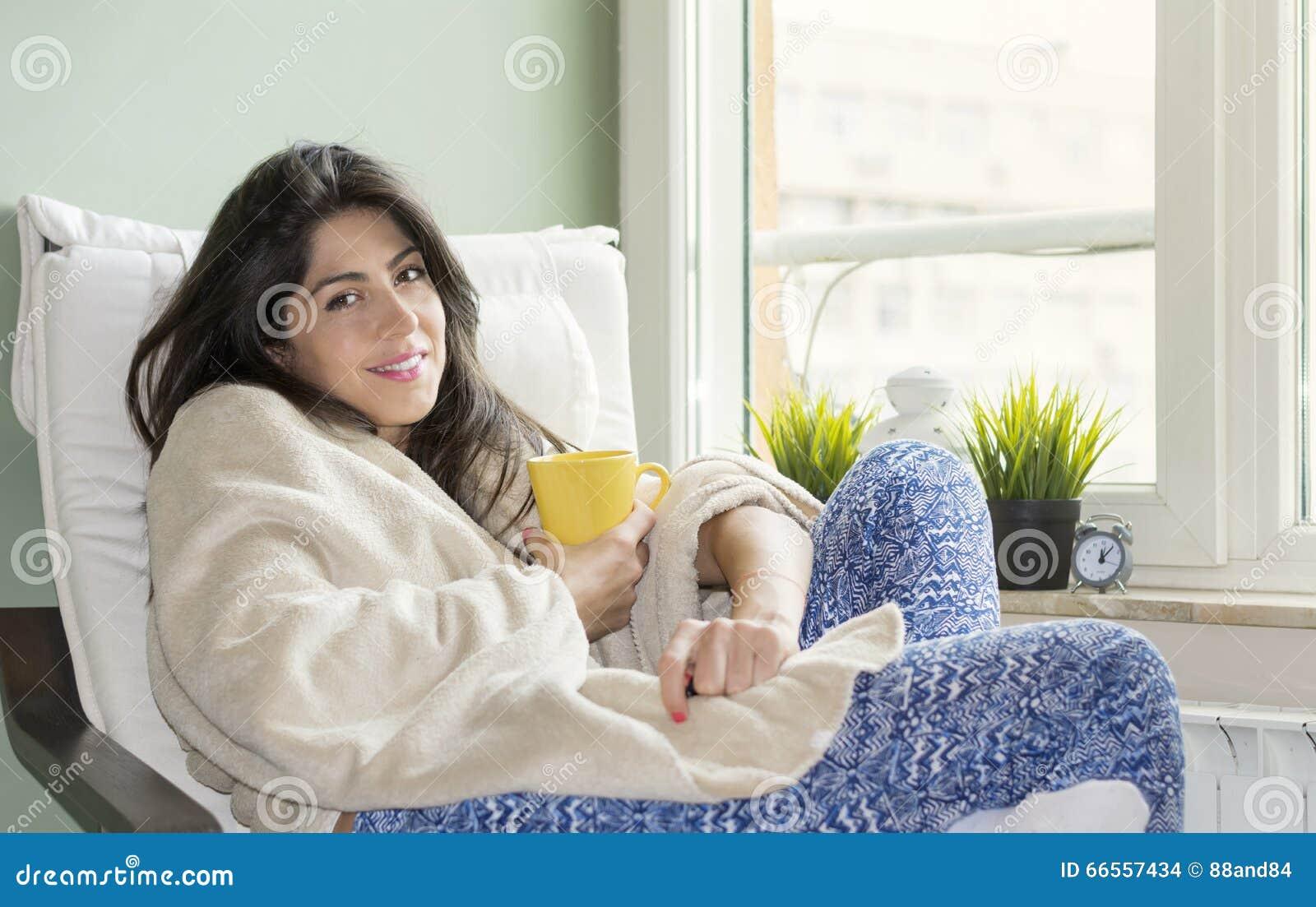 Mulher que senta-se em casa, envolvido em uma cobertura, chá bebendo