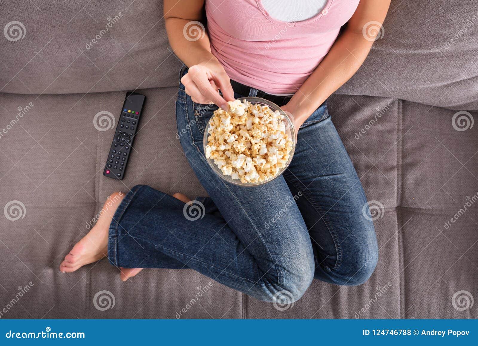 Mulher que senta-se em Sofa Eating Popcorn