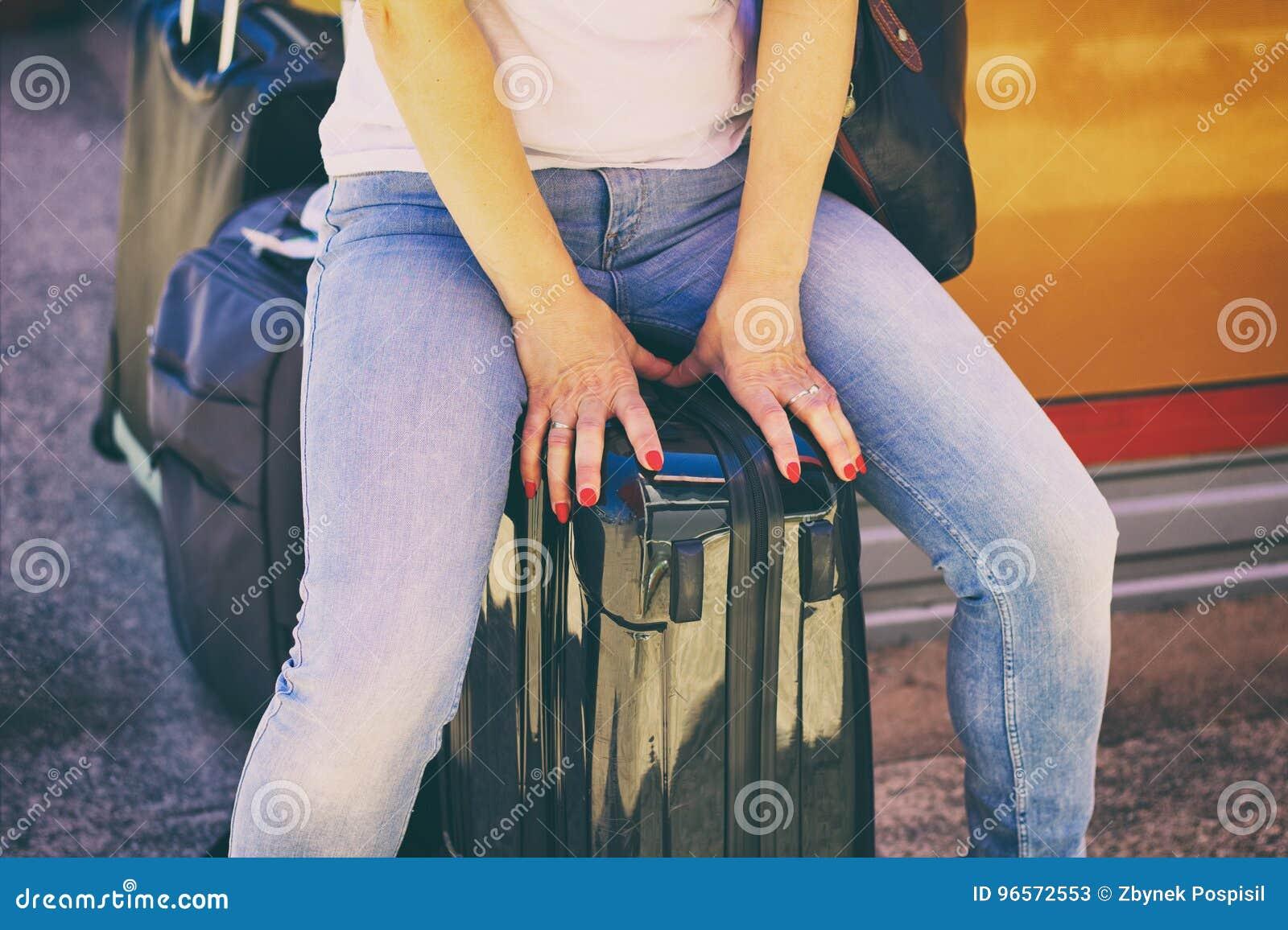 Mulher que senta-se na bagagem