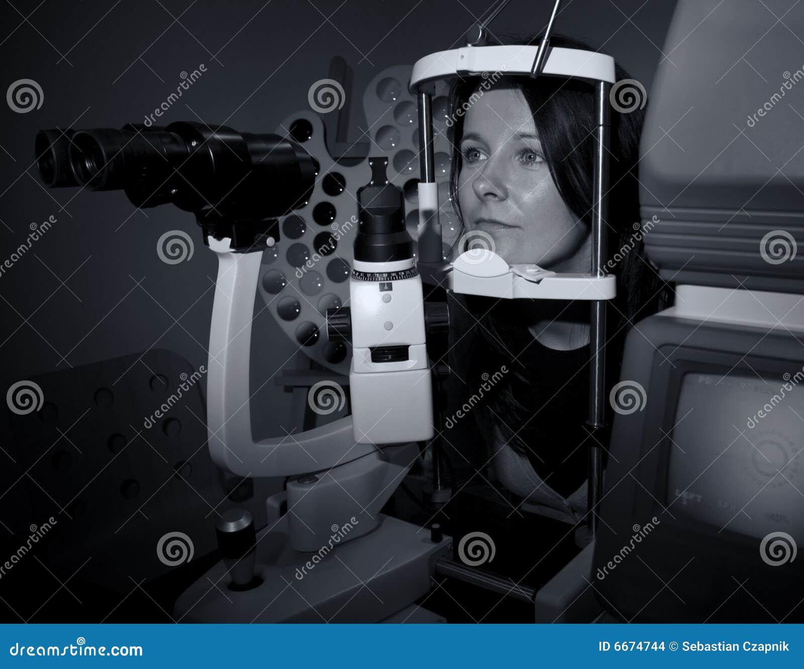 Mulher que senta-se na máquina do óptico