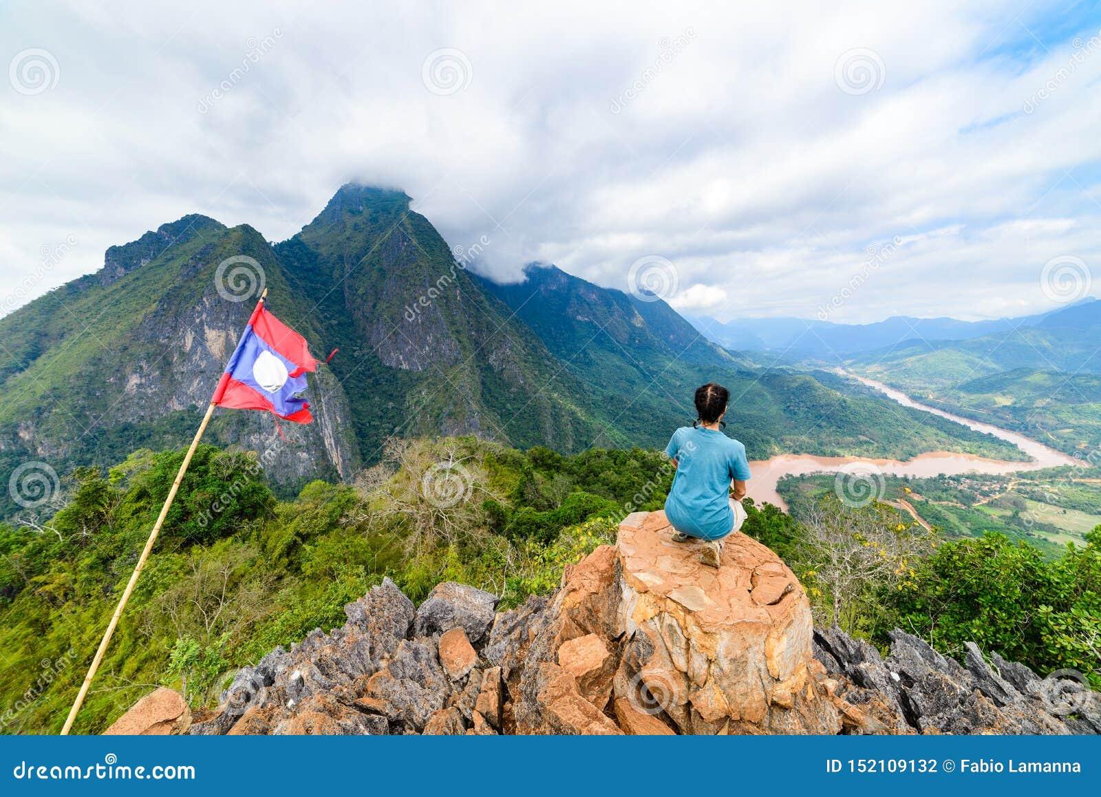 Mulher que senta-se na parte superior da montanha no destino de viagem do curso do conceito dos millenials dos povos maduros de L