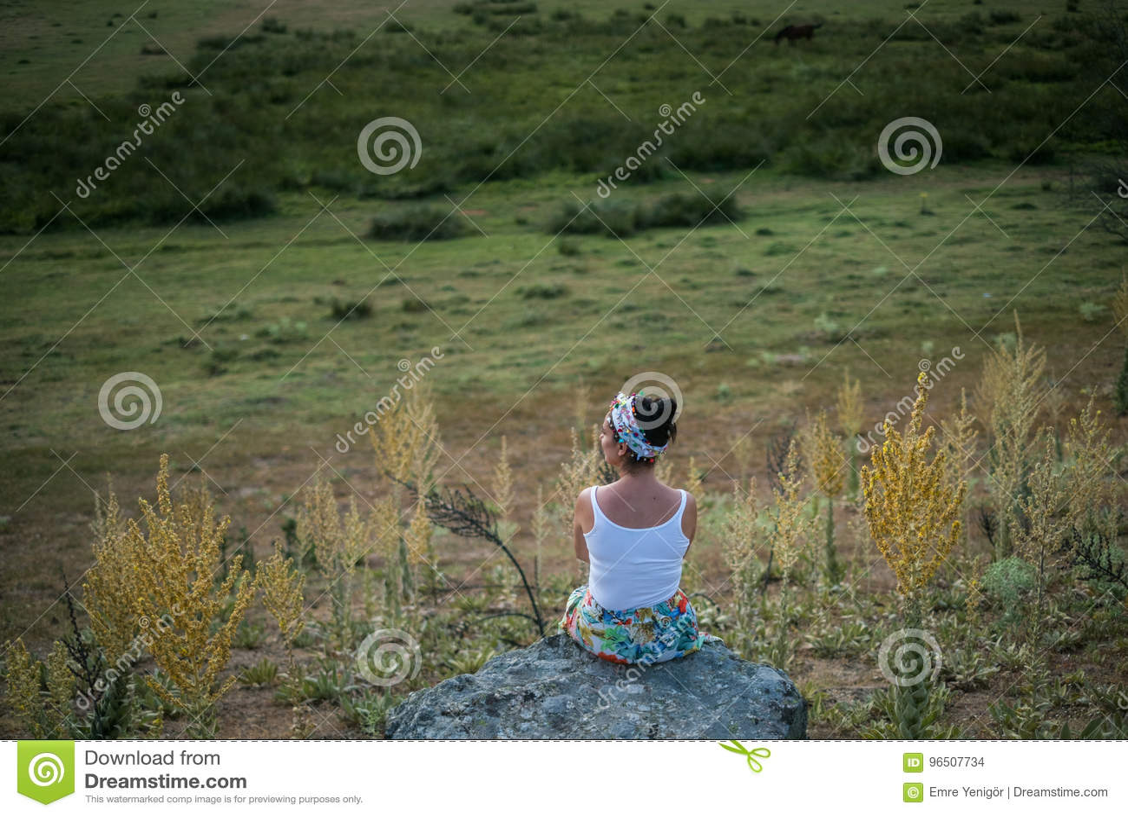 Mulher que senta-se na rocha