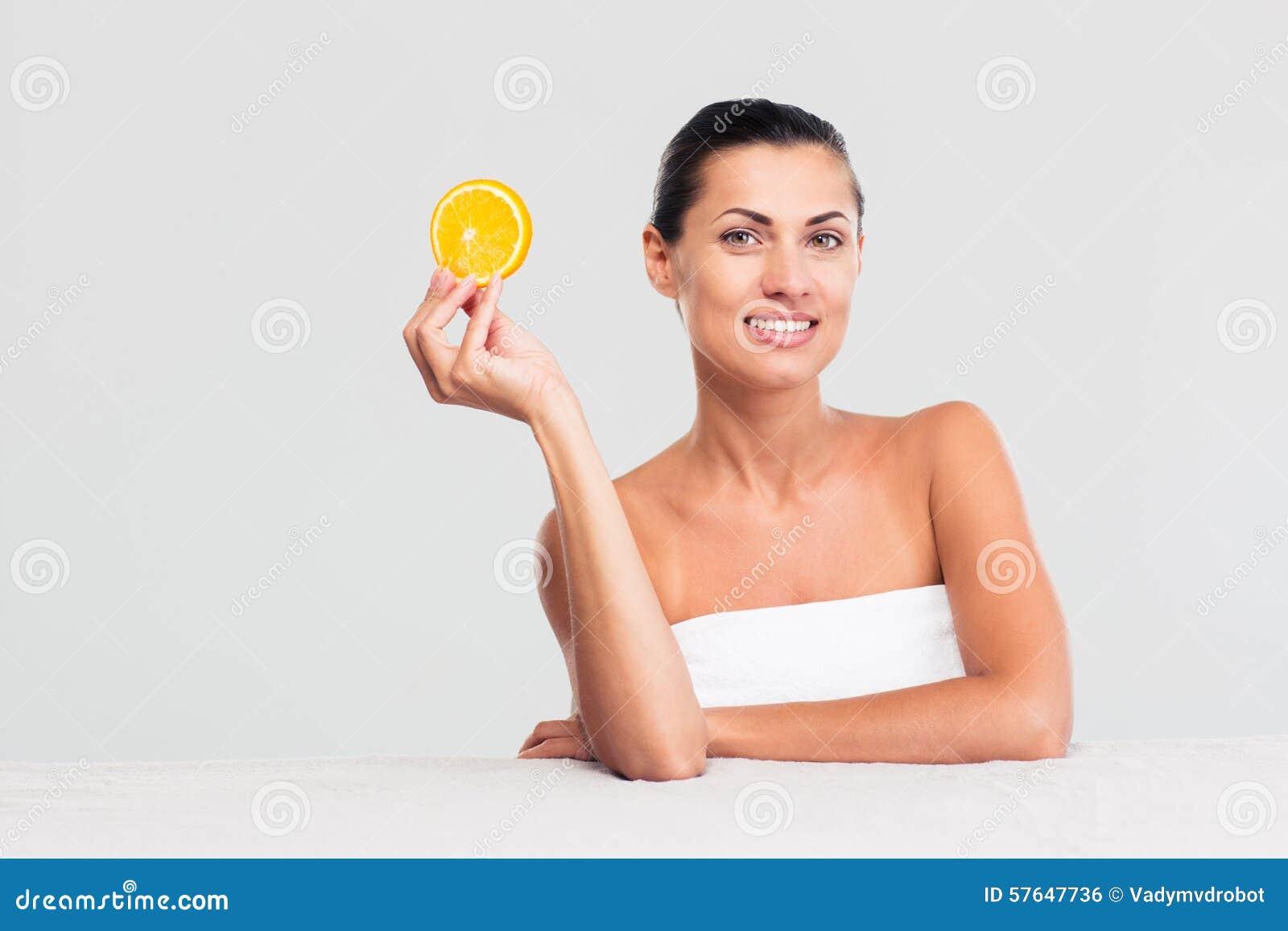 Mulher que senta-se na tabela e que guarda a laranja