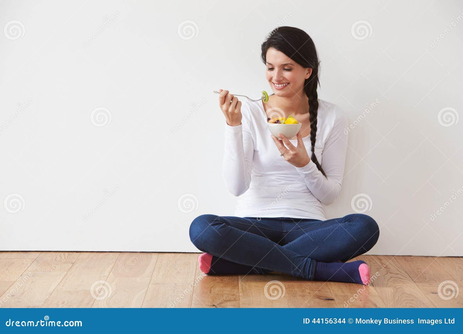 Mulher que senta-se no assoalho que come a bacia de fruto fresco