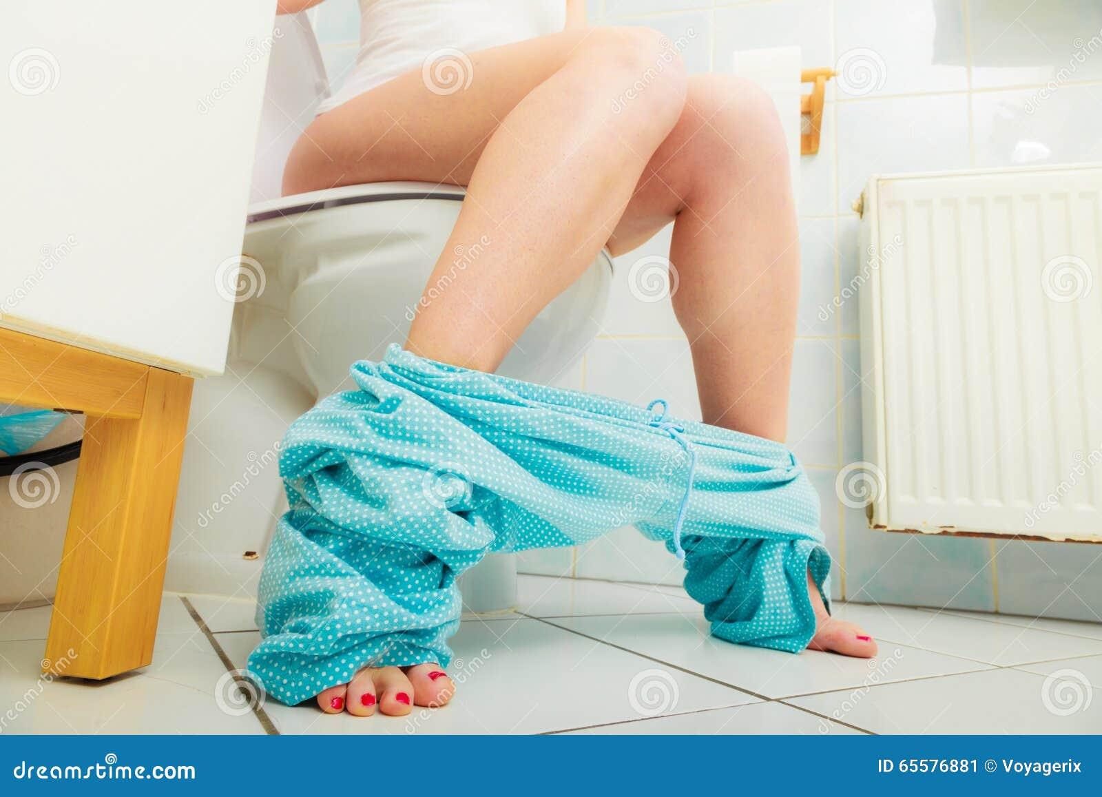 Mulher que senta-se no toalete na manhã