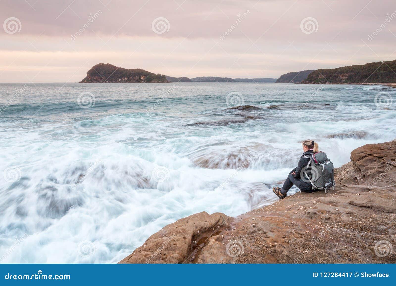 Mulher que senta-se pelo oceano que deixa ondas dobrar em seus pés