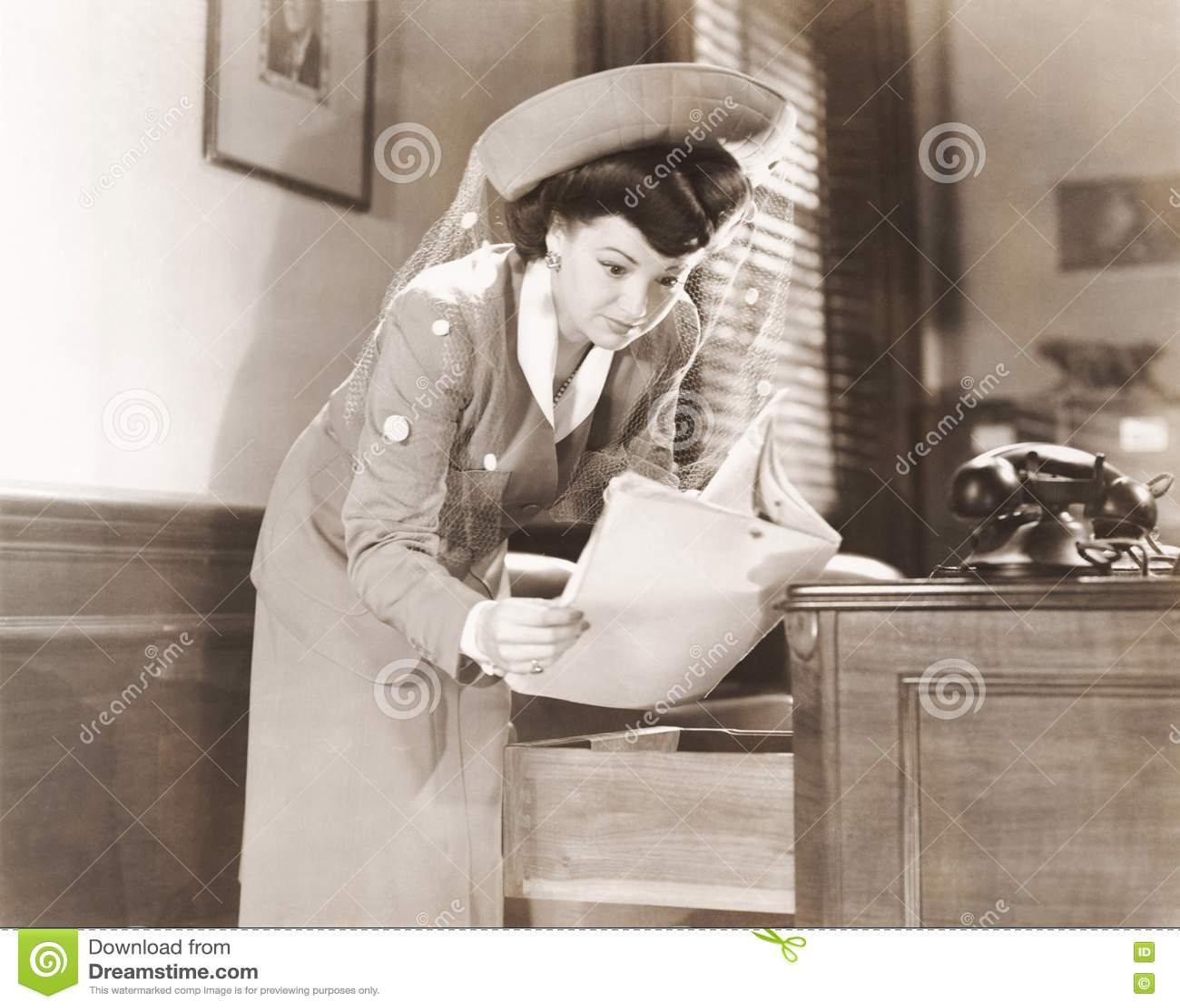 Mulher que sneaking um olhar em originais no escritório