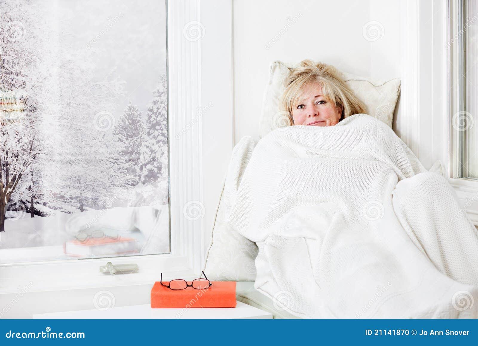 Mulher que snuggling sob um cobertor
