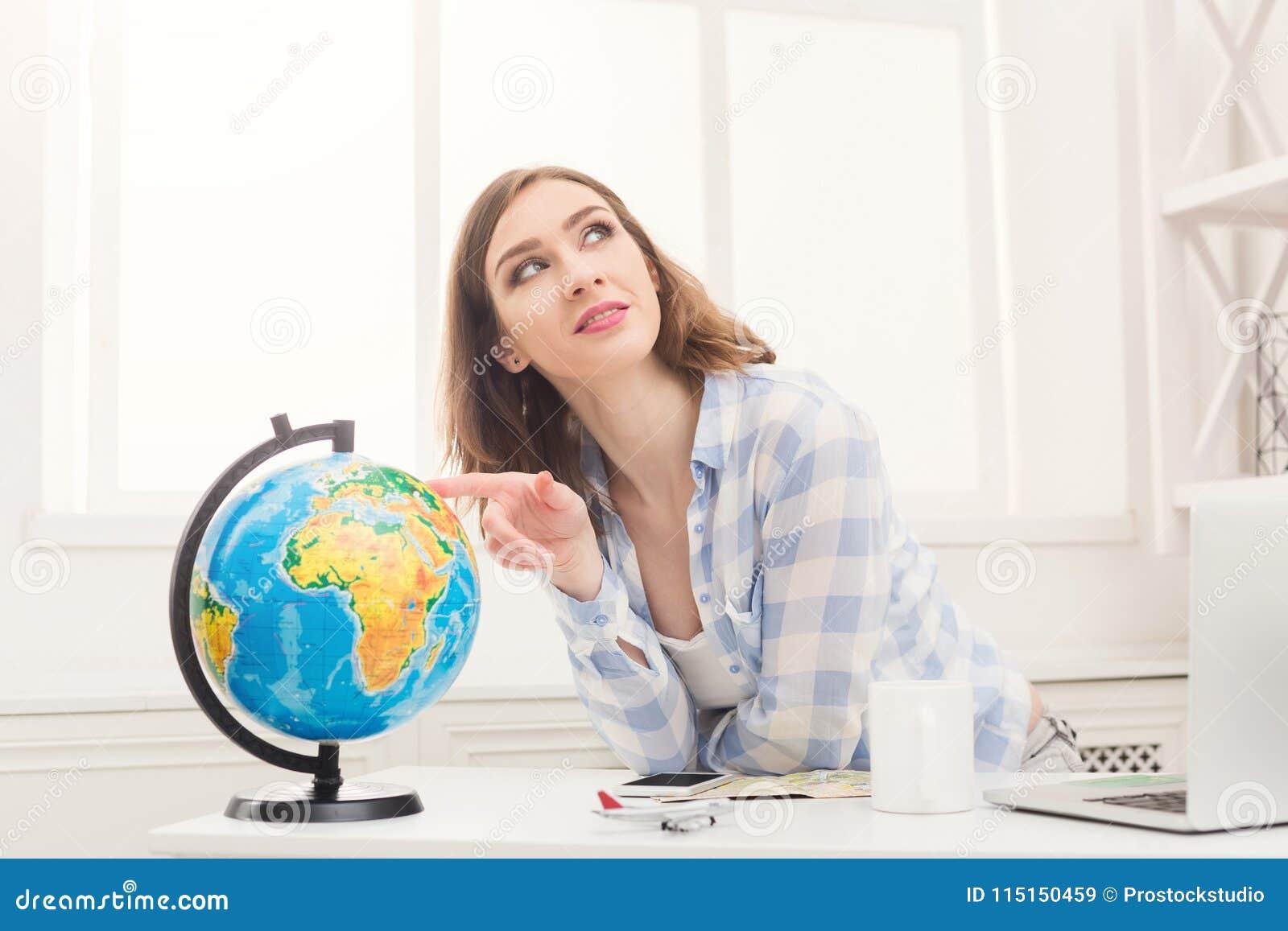 Mulher que sonha sobre o curso, olhando o globo
