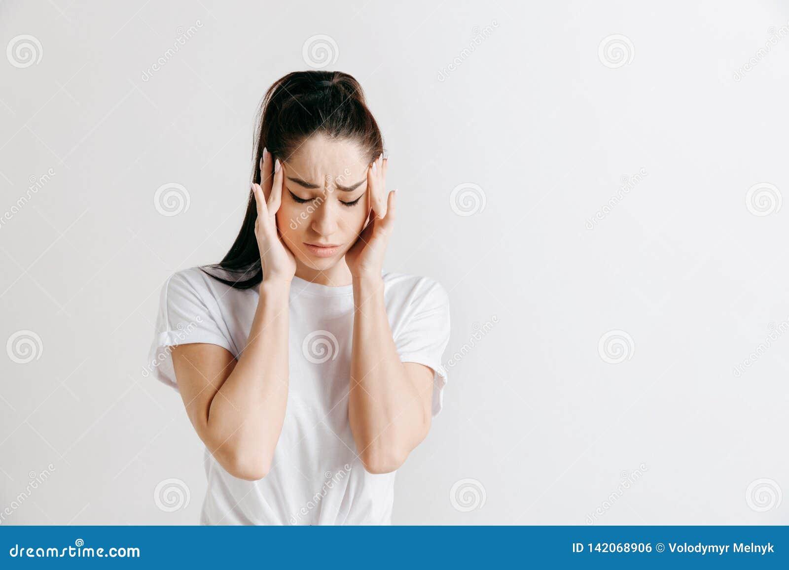 Mulher que tem a dor de cabeça Sobre o fundo cinzento