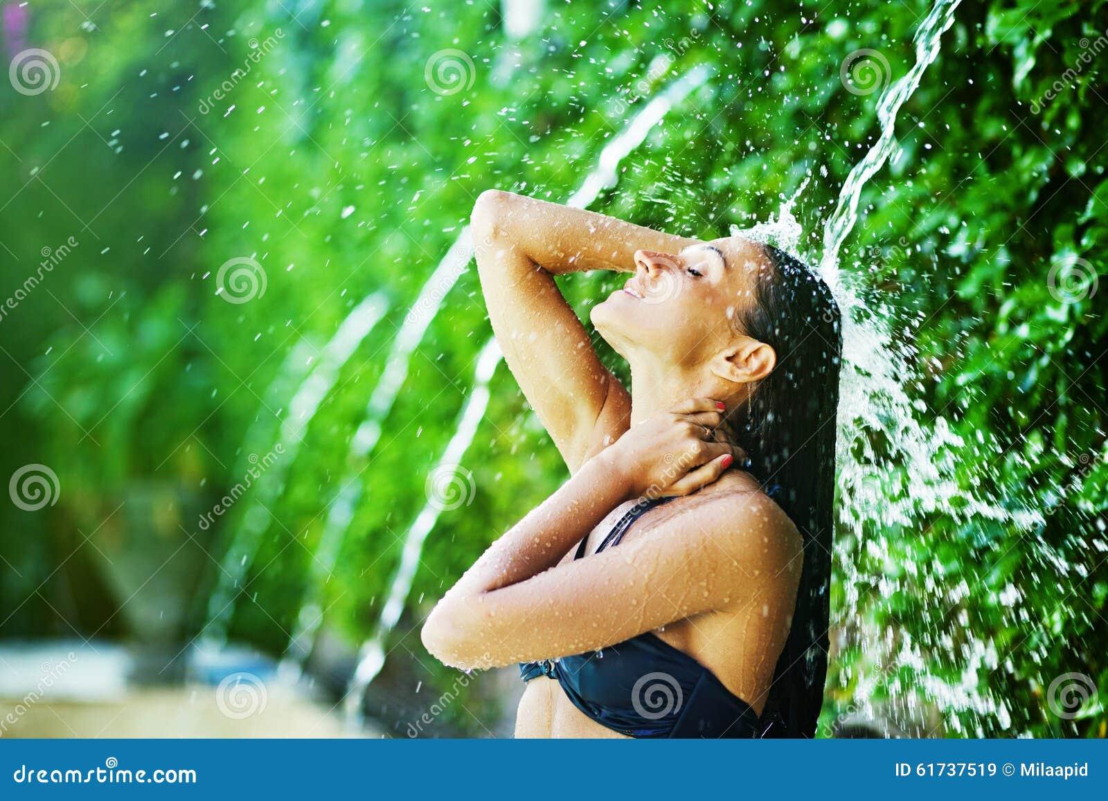 Mulher que tem o chuveiro sob a cachoeira tropical