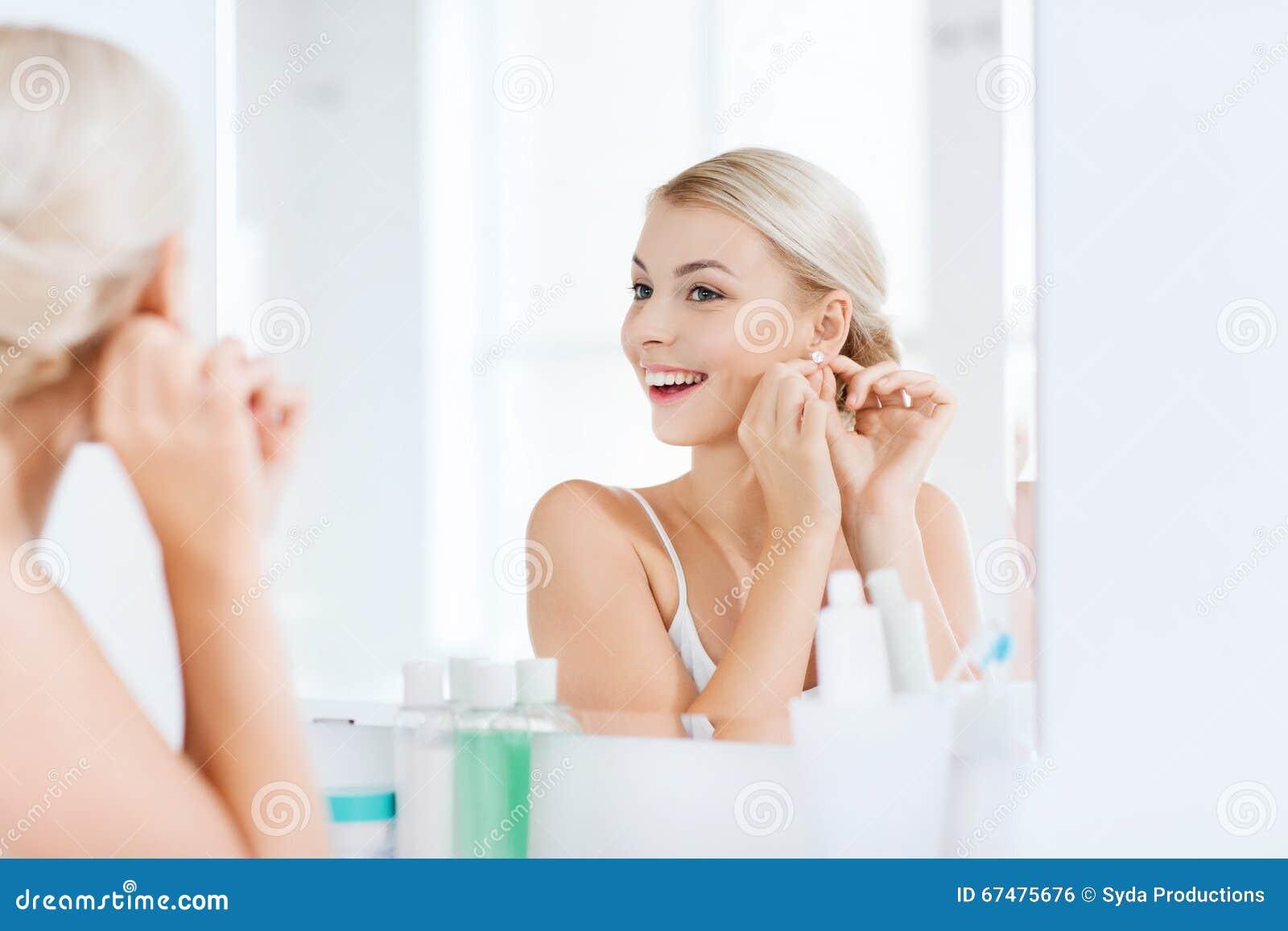 Mulher que tenta no brinco que olha o espelho do banheiro