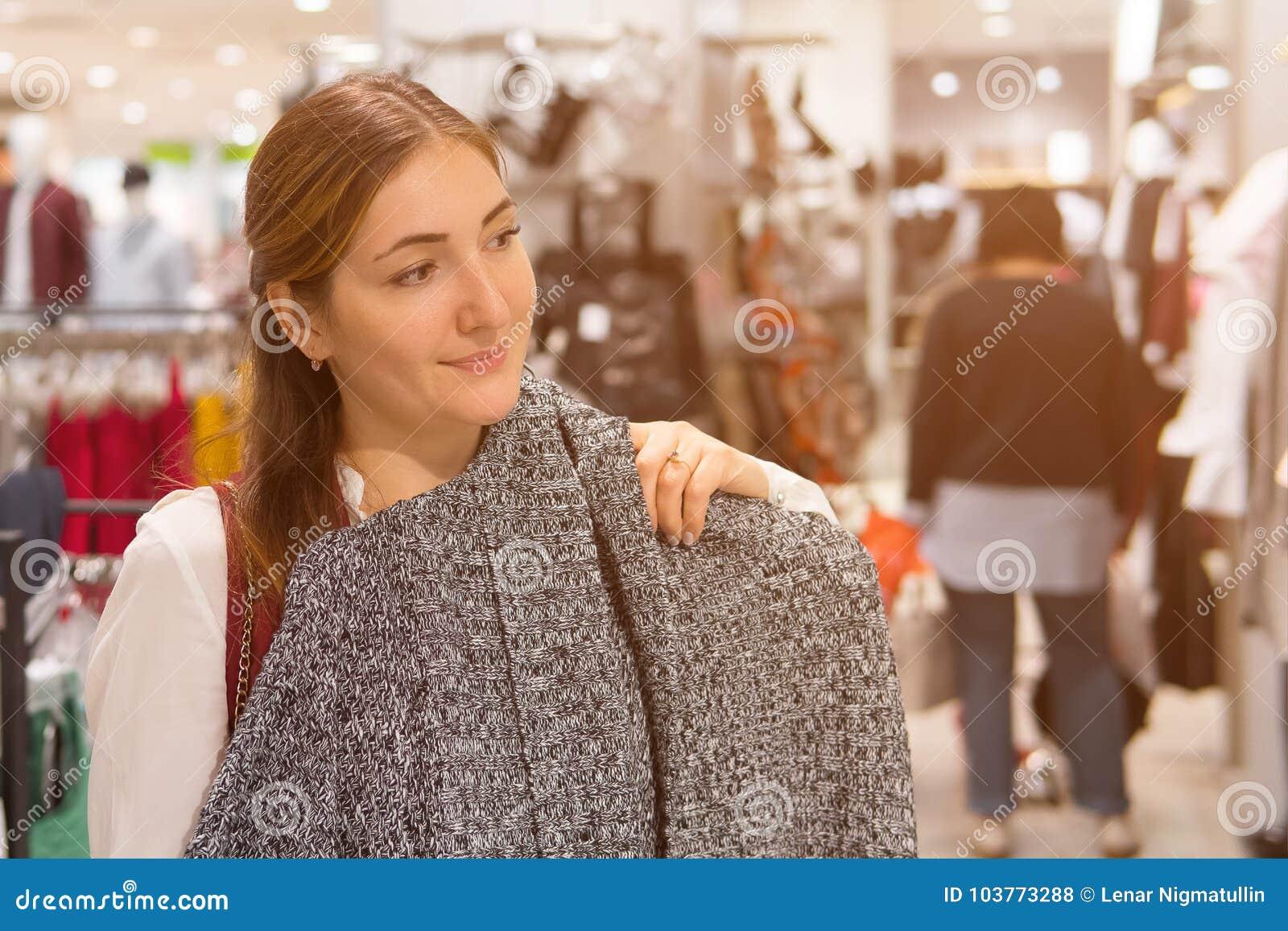 Mulher que tenta no revestimento de lã na loja da roupa