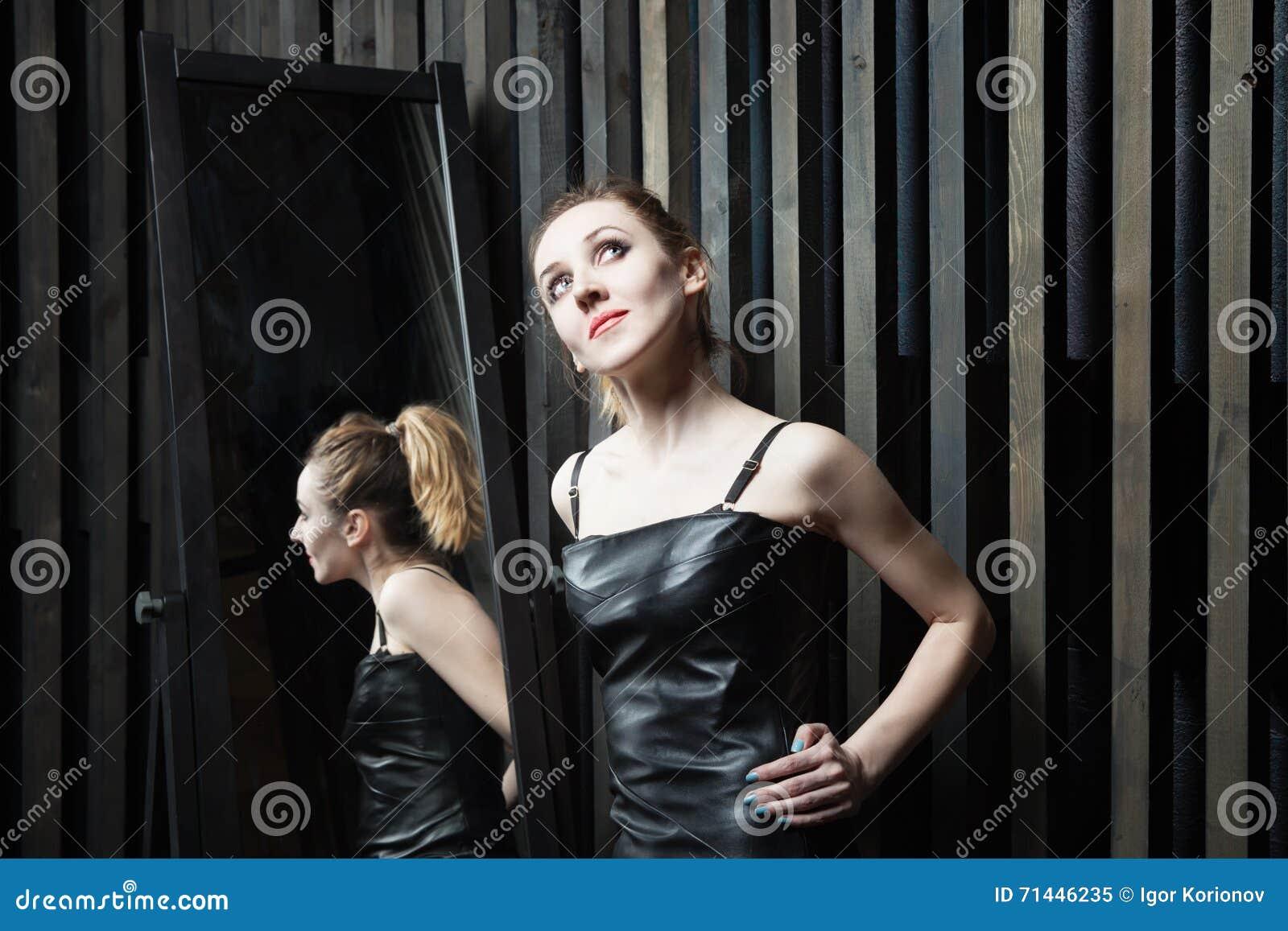 Mulher que tenta no vestido na frente do espelho