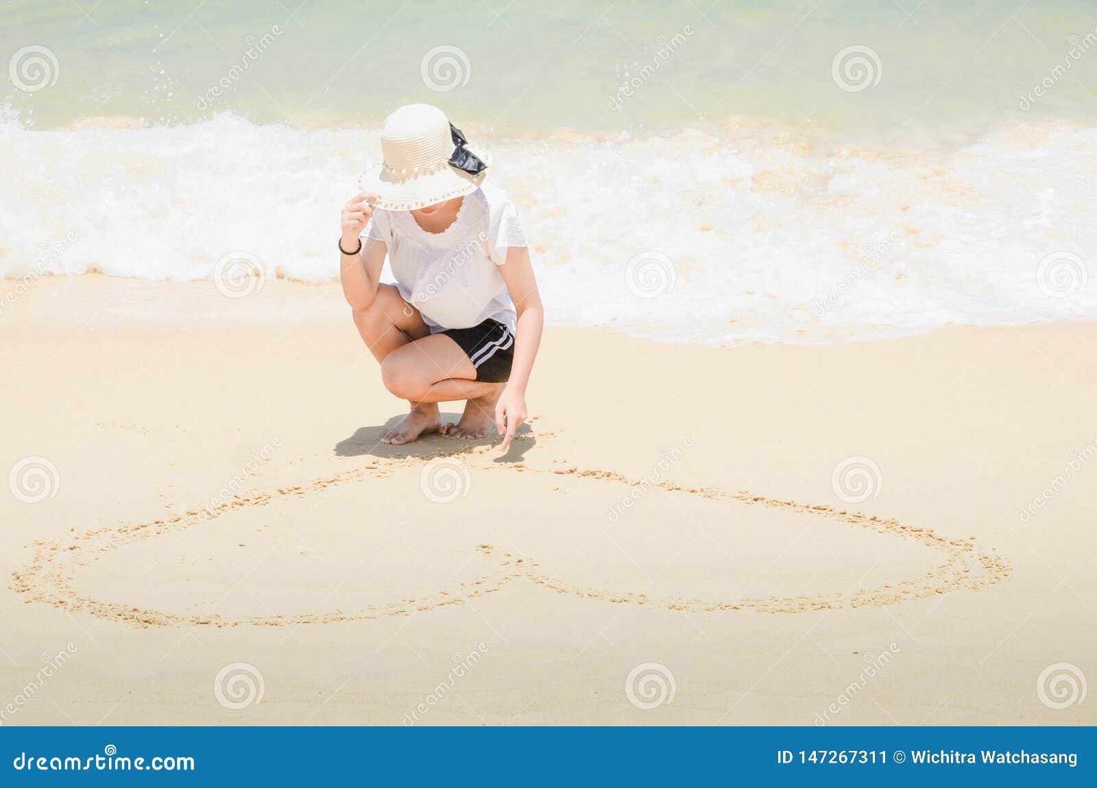 Mulher que tira um coração na areia na praia
