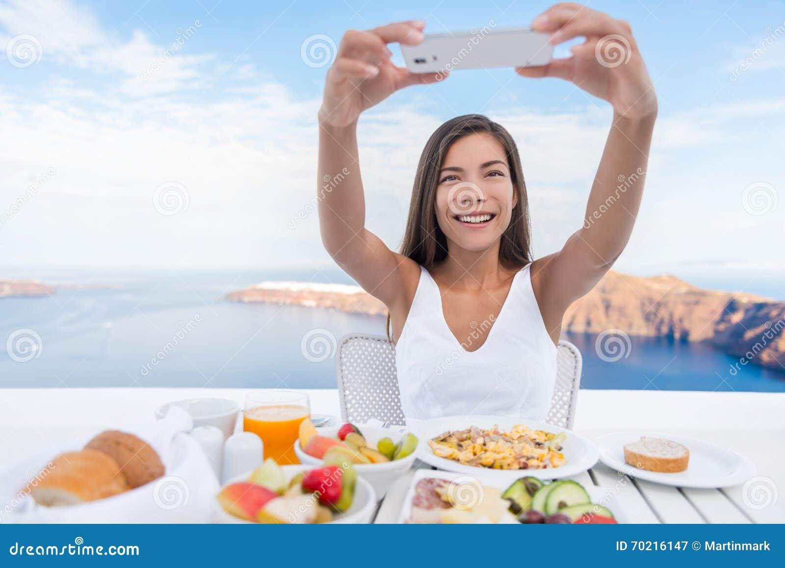 Mulher que toma a foto do café da manhã no telefone esperto App