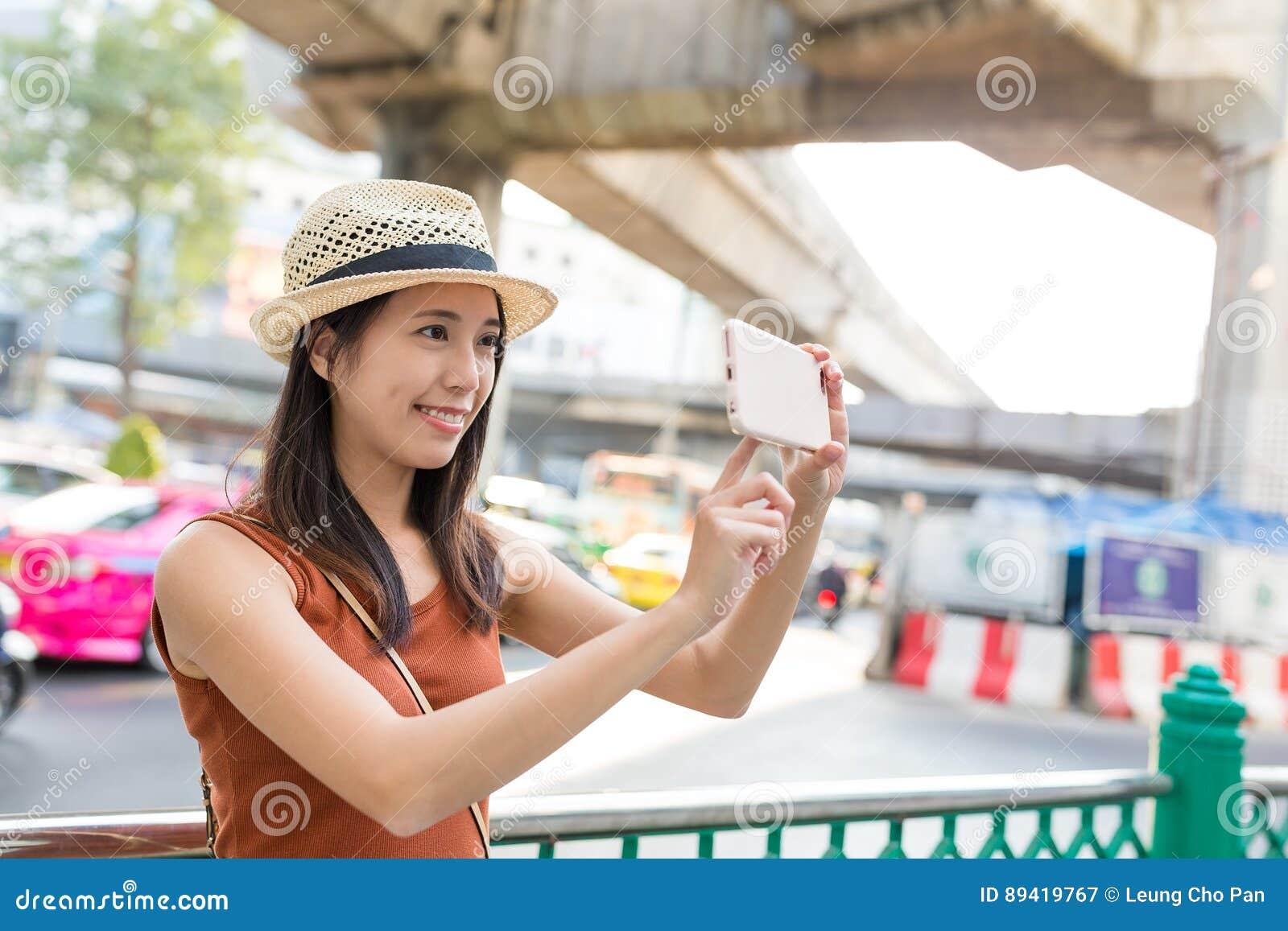 Mulher que toma a foto na cidade de Banguecoque