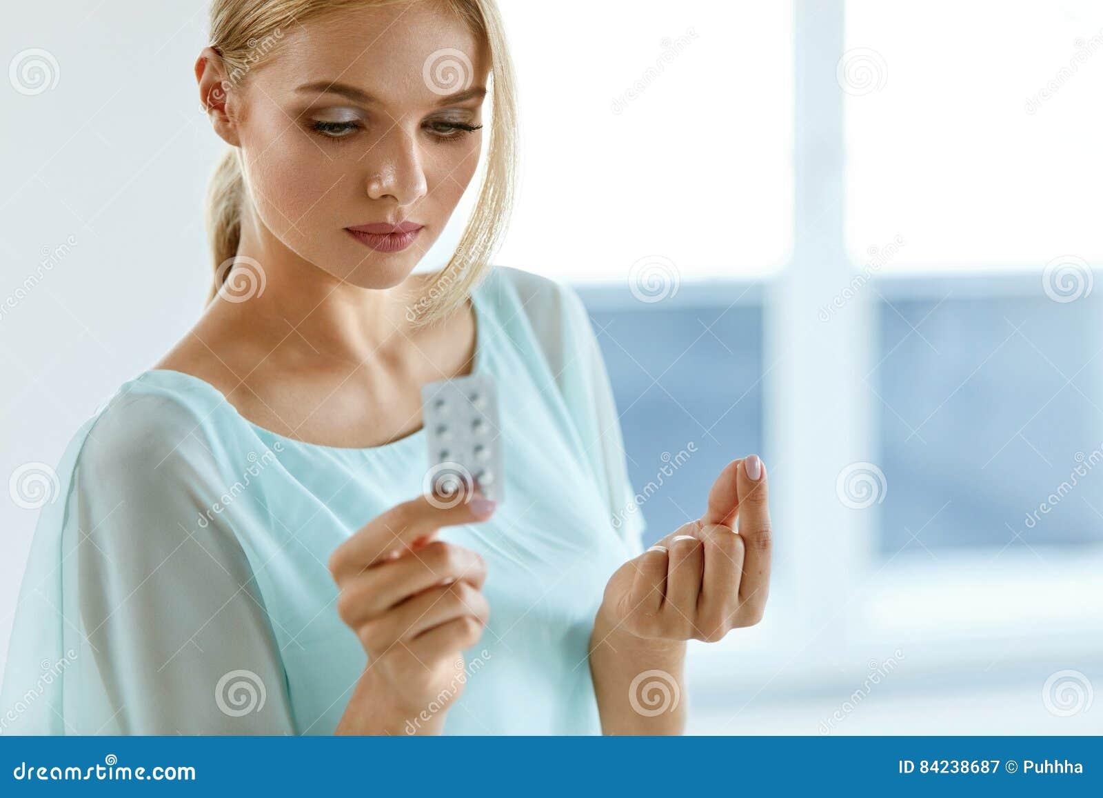 Mulher que toma a medicina Menina bonita com bloco do comprimido com comprimidos