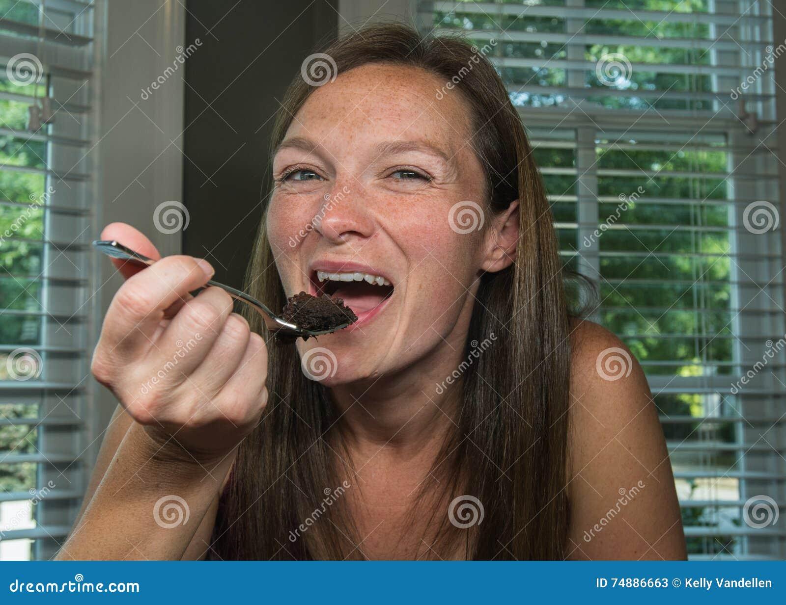 Mulher que toma a mordida do bolo de chocolate