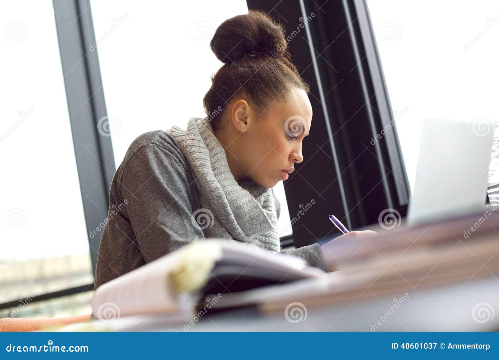 Mulher que toma a notas para ela o estudo