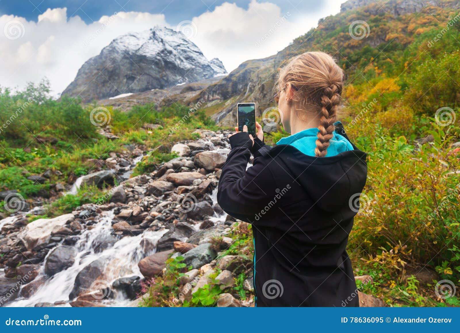 Mulher que toma uma foto da montanha no smartphone