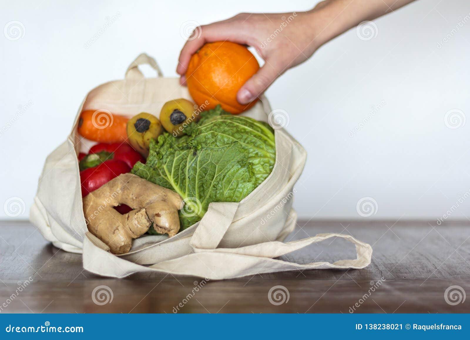 Mulher que toma uma laranja do saco do eco com mantimentos
