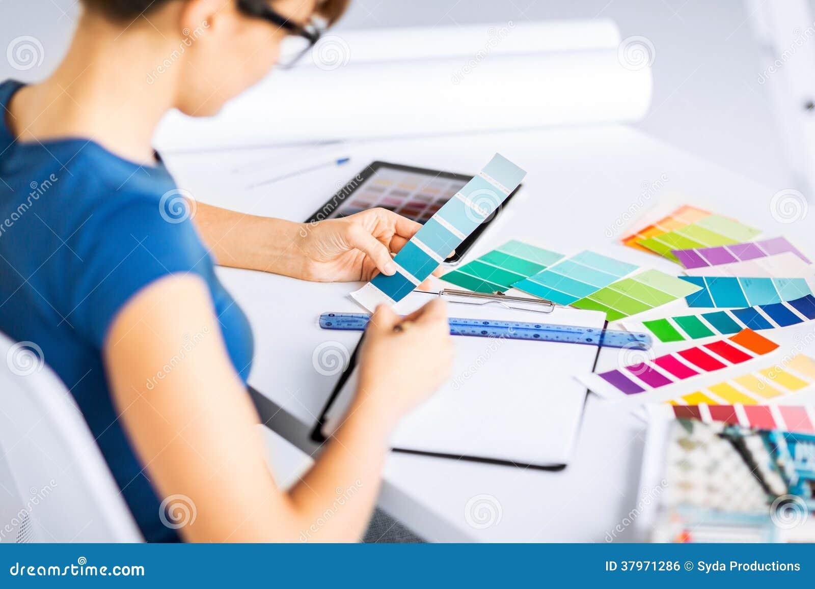Mulher que trabalha com as amostras da cor para a seleção