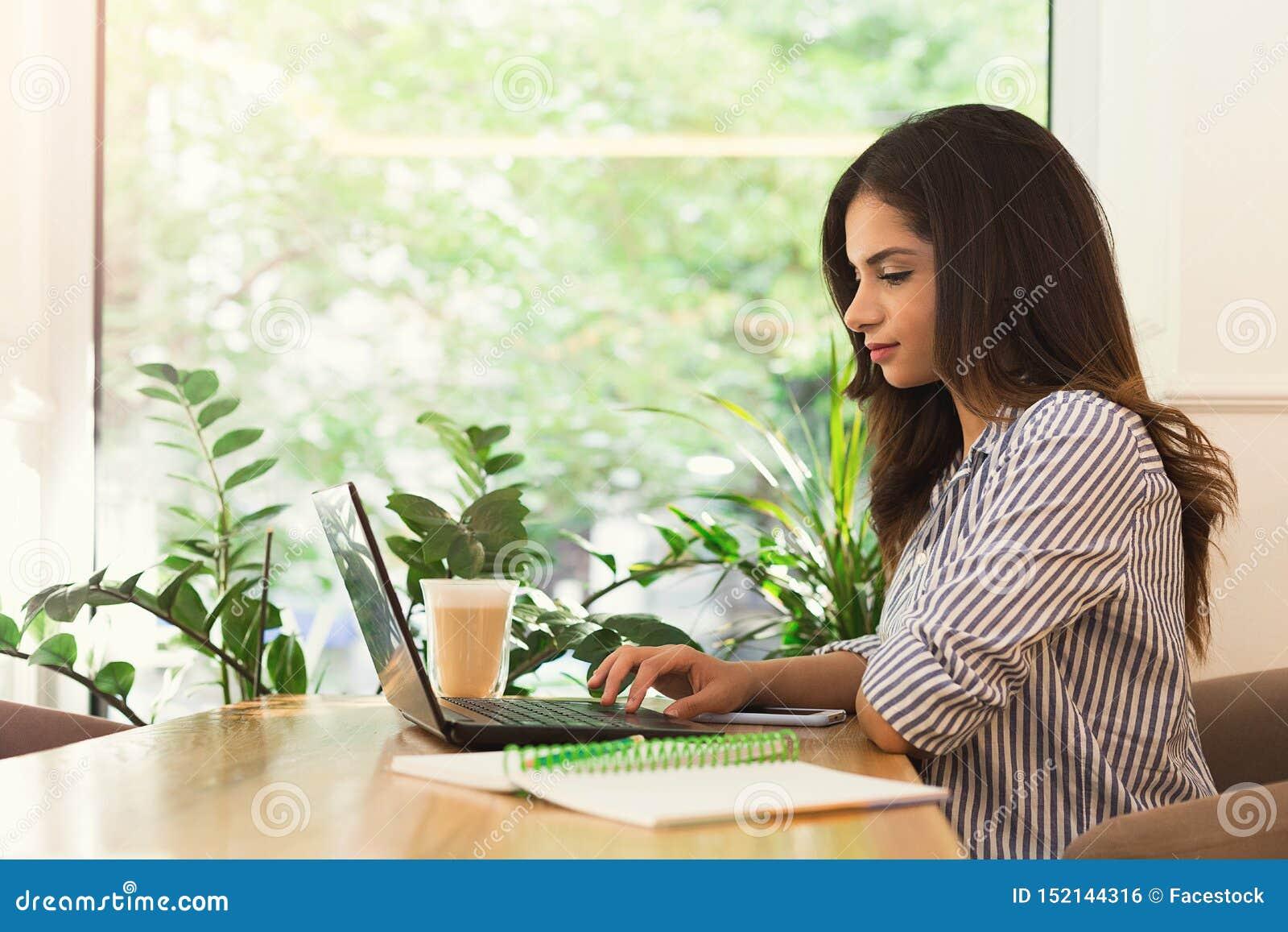 Mulher que trabalha no computador, usando a tecnologia fora