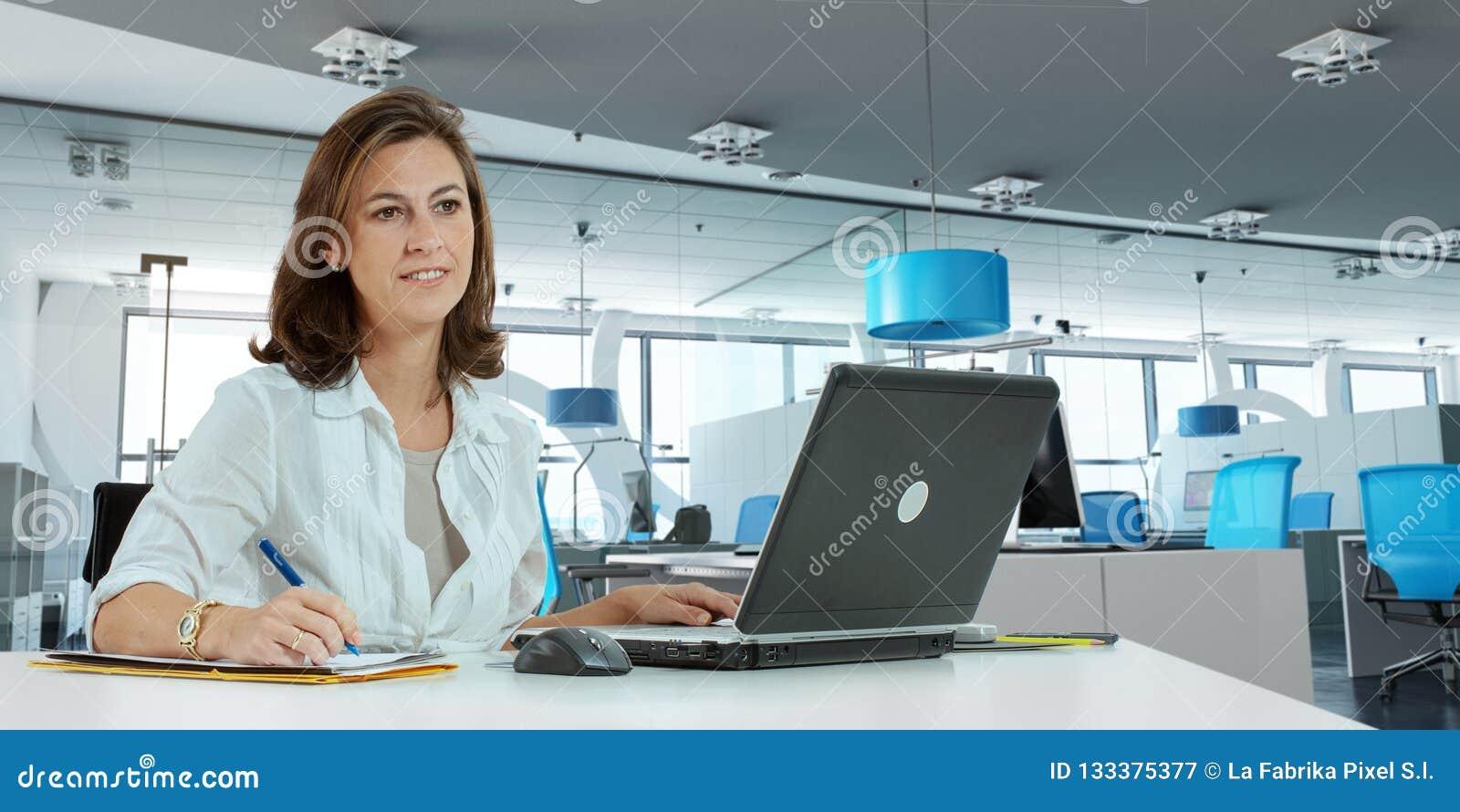 Mulher que trabalha no escritório moderno