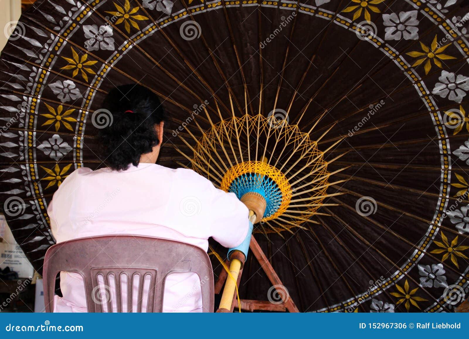 Mulher que trabalha no guarda-chuva de papel enorme em Chiang Mai, Tailândia