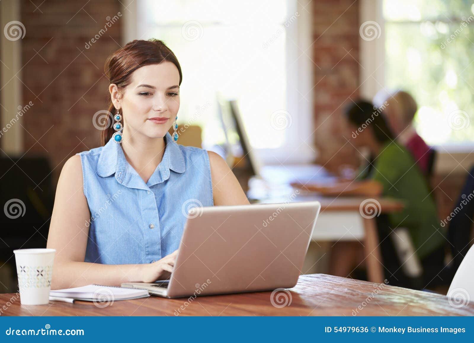 Mulher que trabalha no portátil no escritório contemporâneo