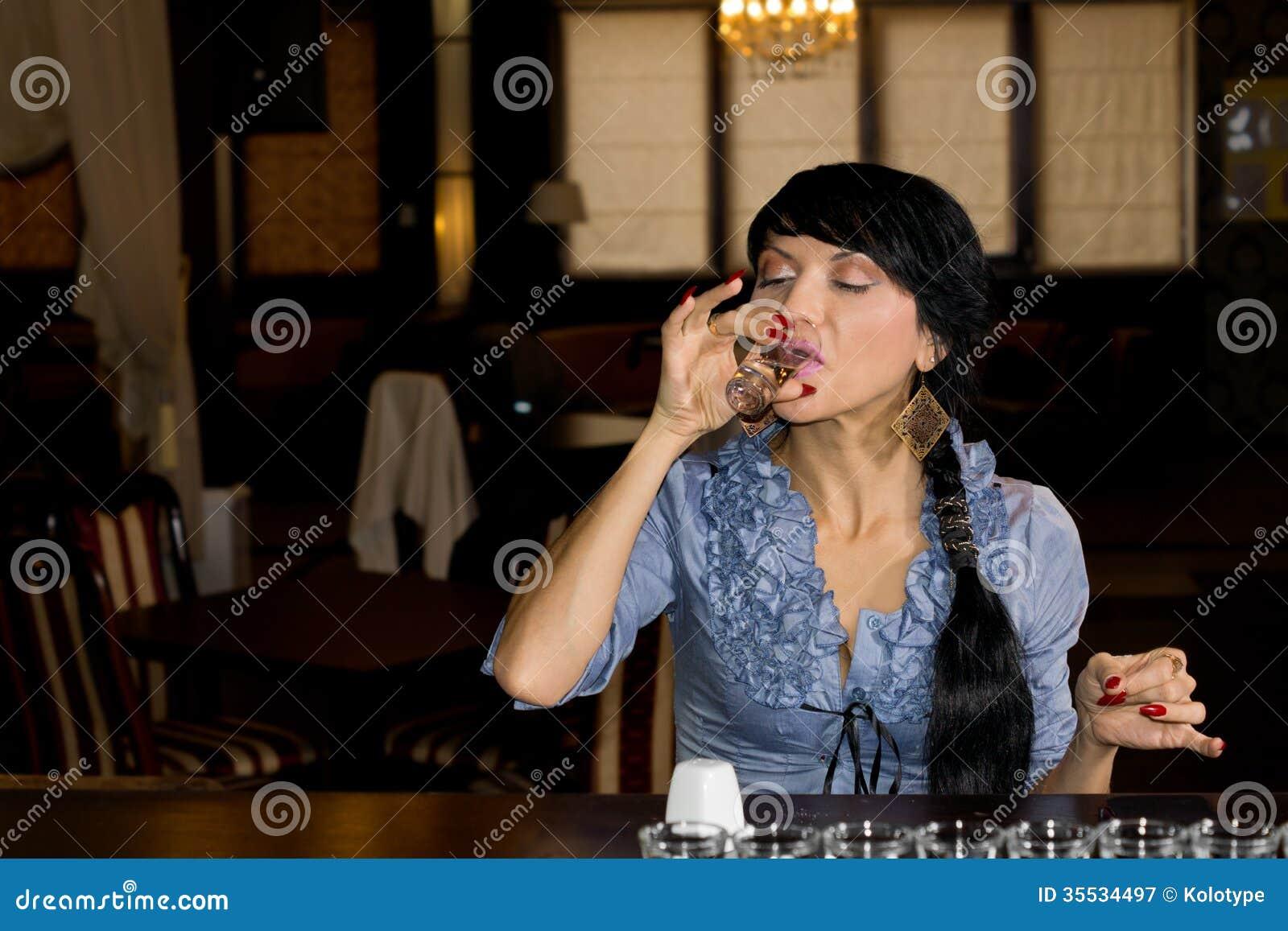 Mulher que traga um vidro da vodca pura
