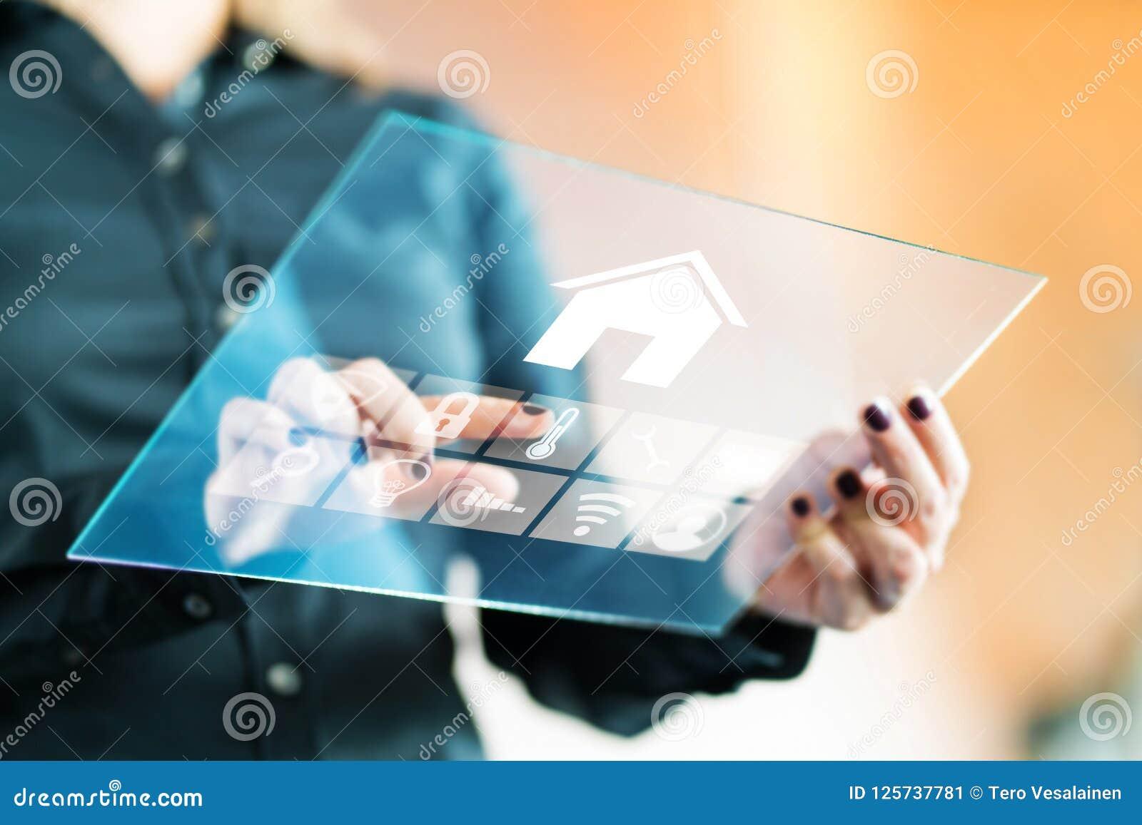 Mulher que usa a aplicação esperta do controle da casa com a tabuleta de vidro transparente futurista